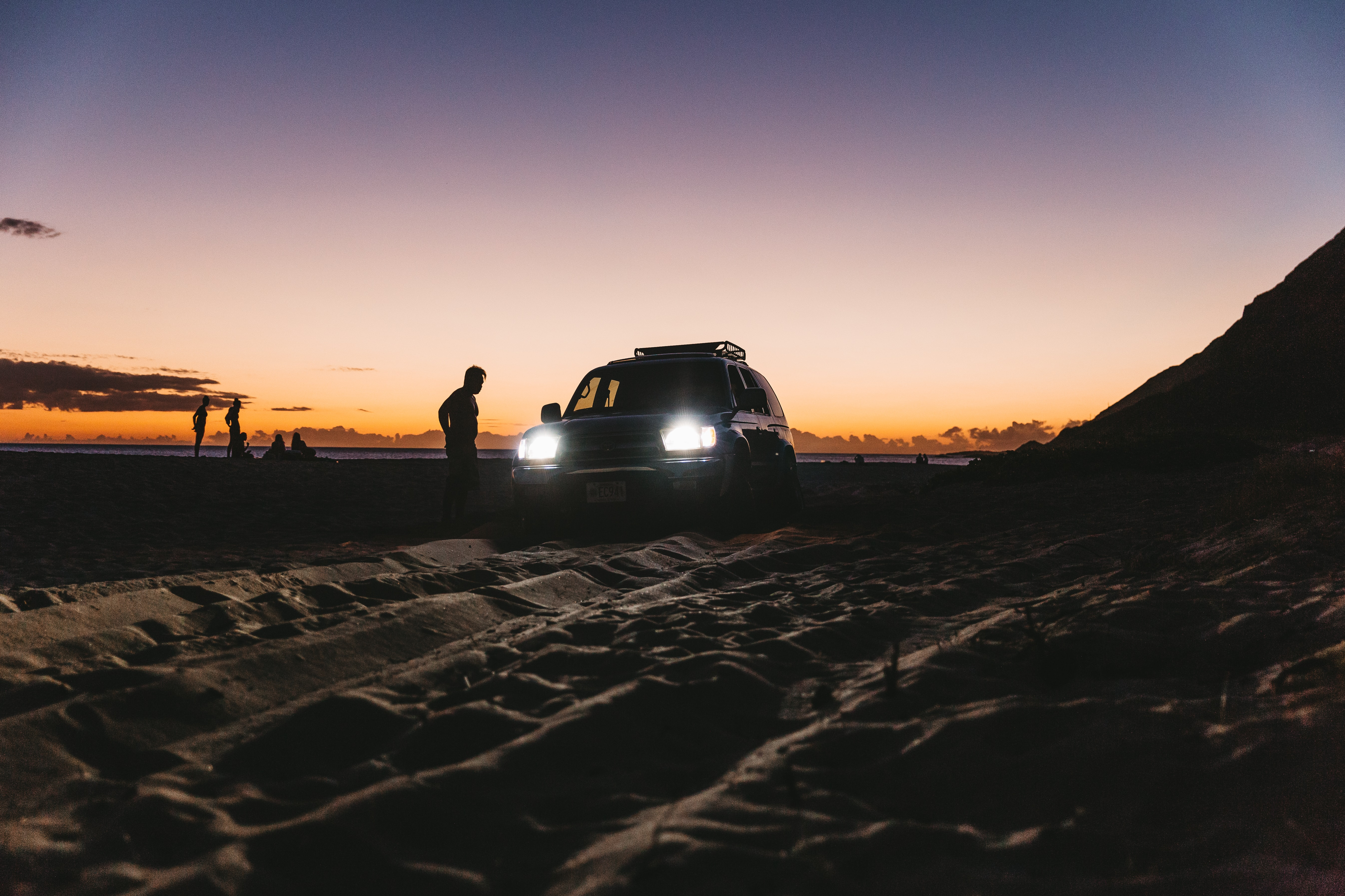 A person standing next to a car with their lights on on a beach at dusk in Honolulu
