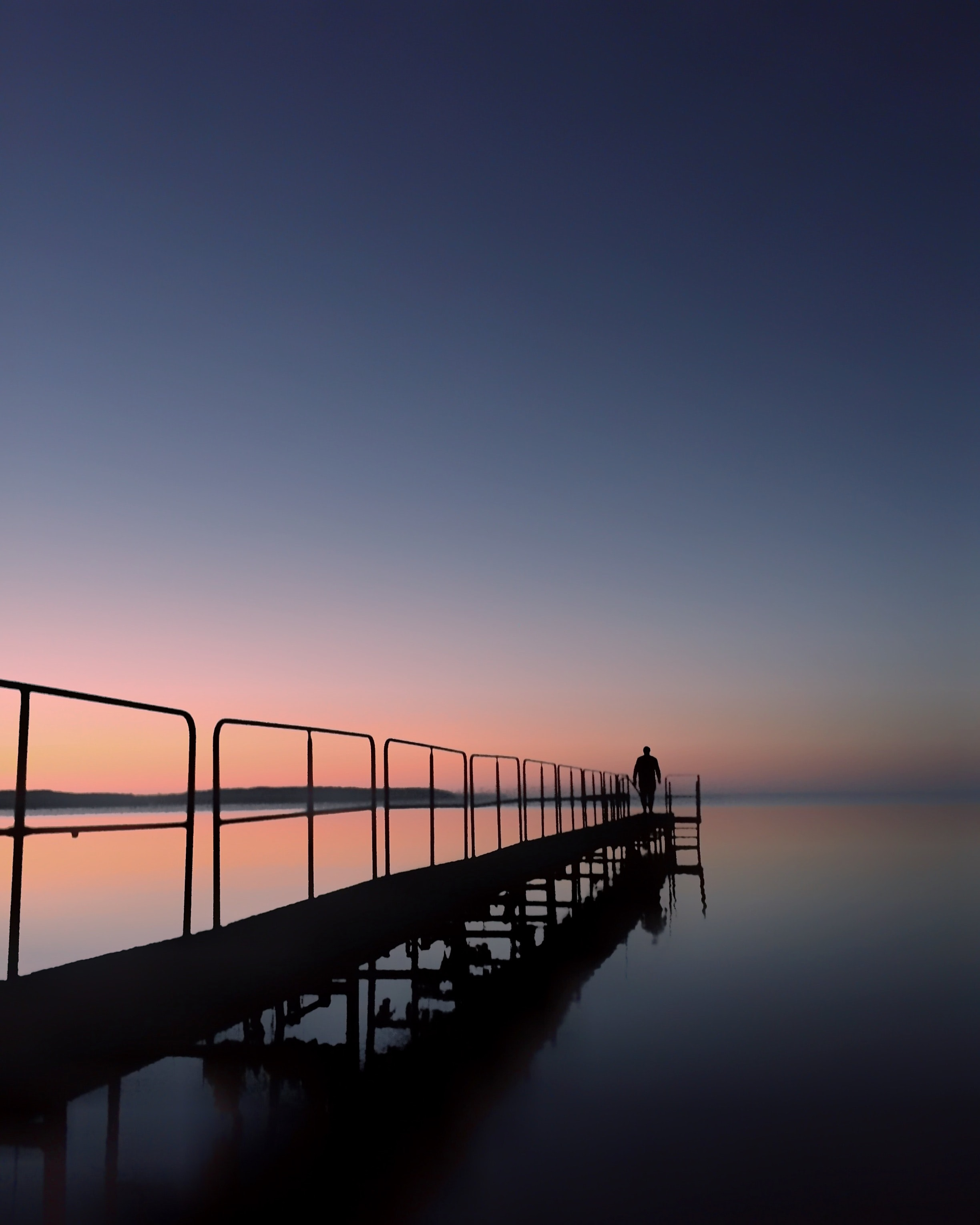 silhouette photo of person standing on dock