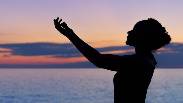 silhouette of woman raising her right hand
