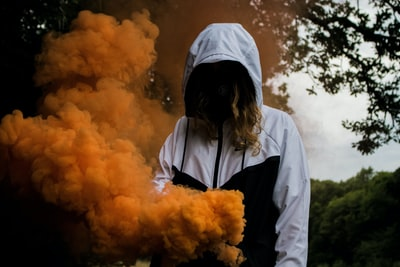 woman in black and white zip-up hoodie near orange smokes under a tree smoke grenade teams background