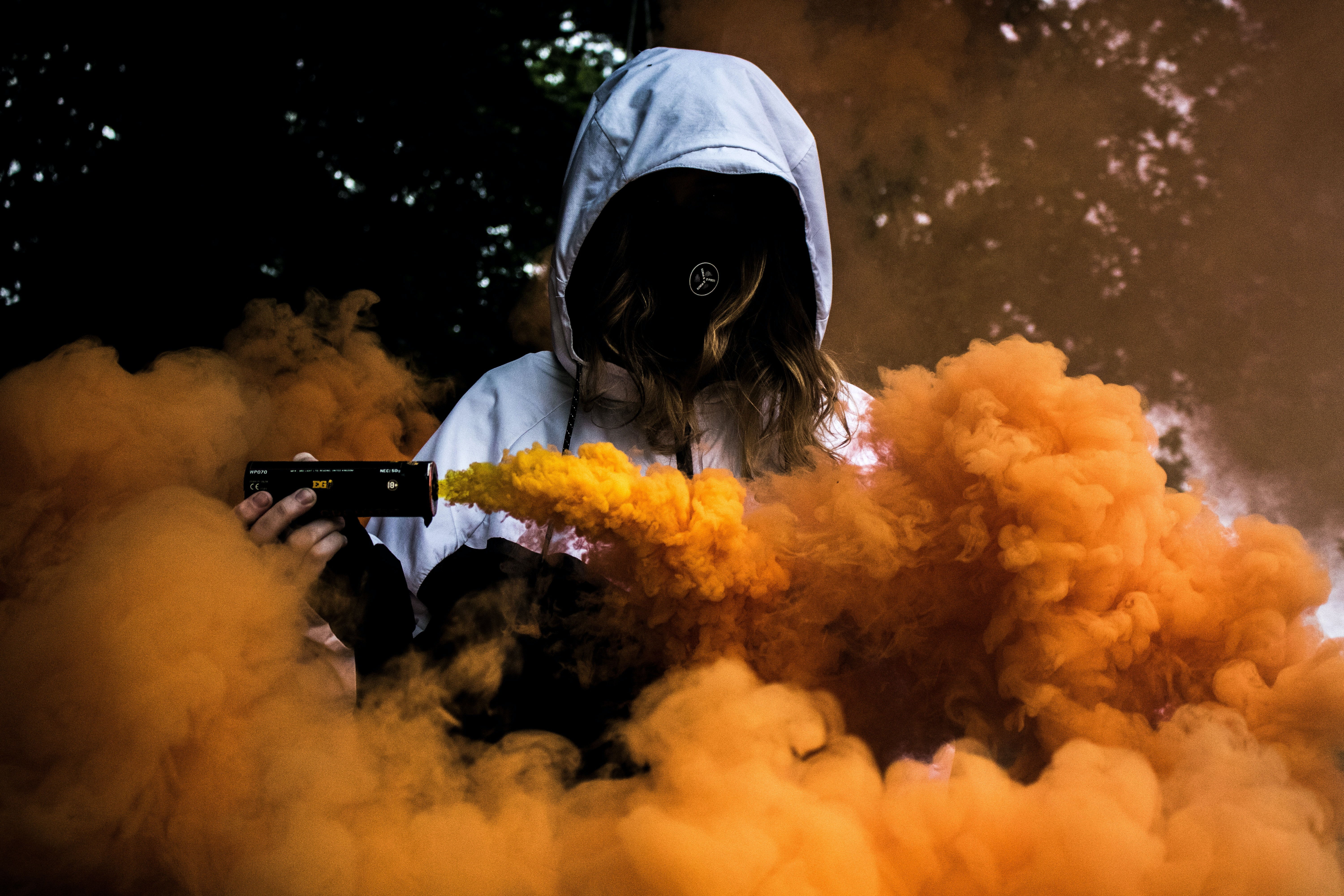 A hooded person is surrounded by orange smoke from a smoke grenade in Mostyn
