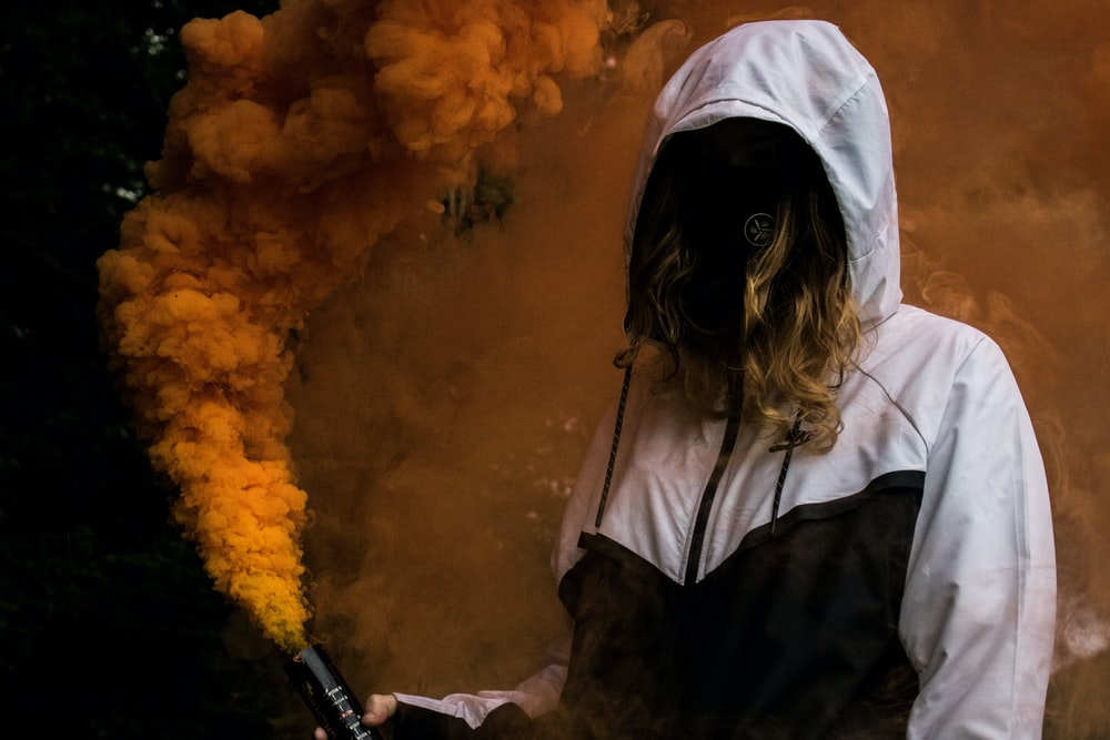 person holding orange smoke