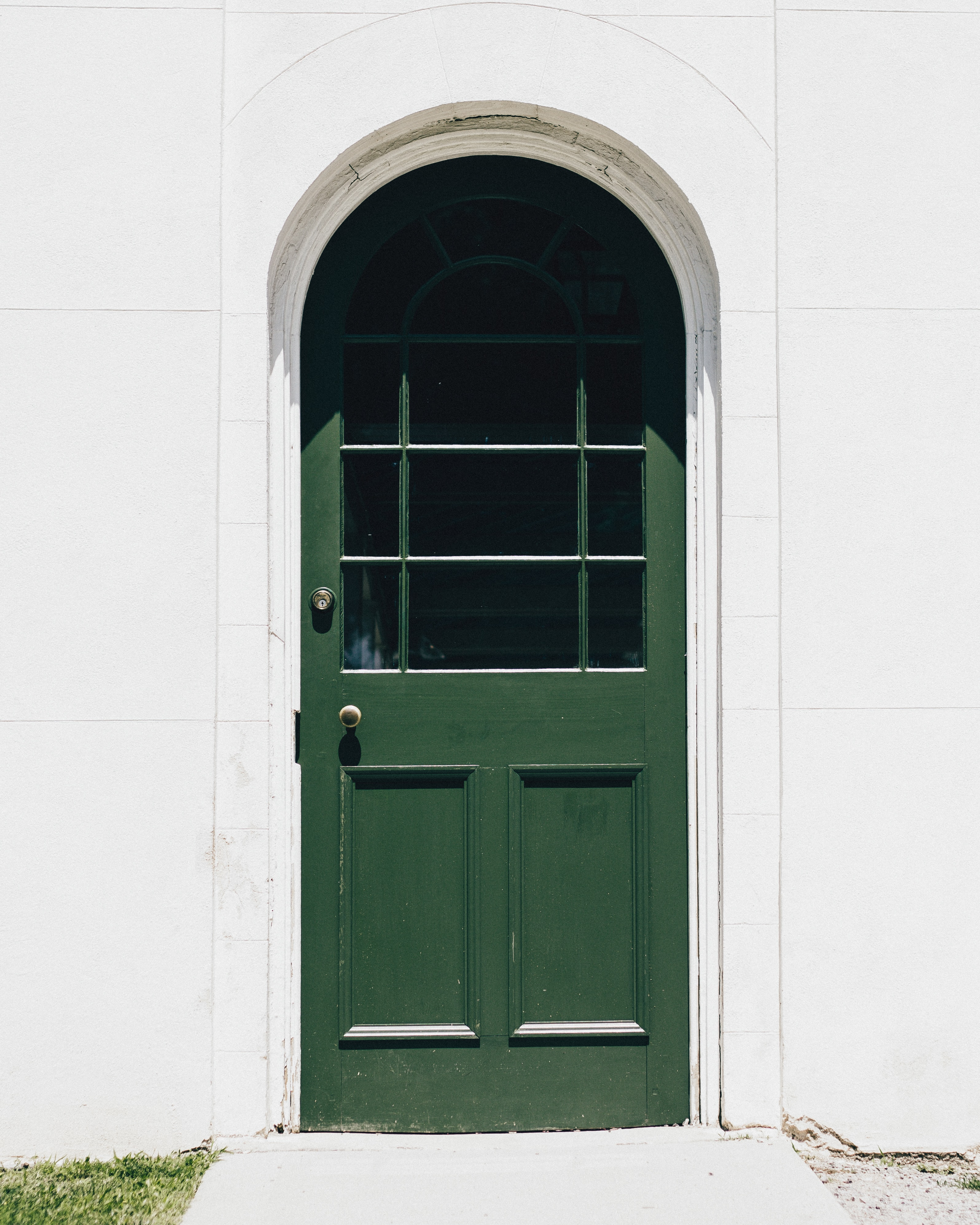 White arched doorway with a green door and windows on the top half and grass next to the sidewalk