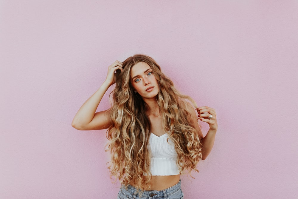 woman standing next to pink wall while scratching her head