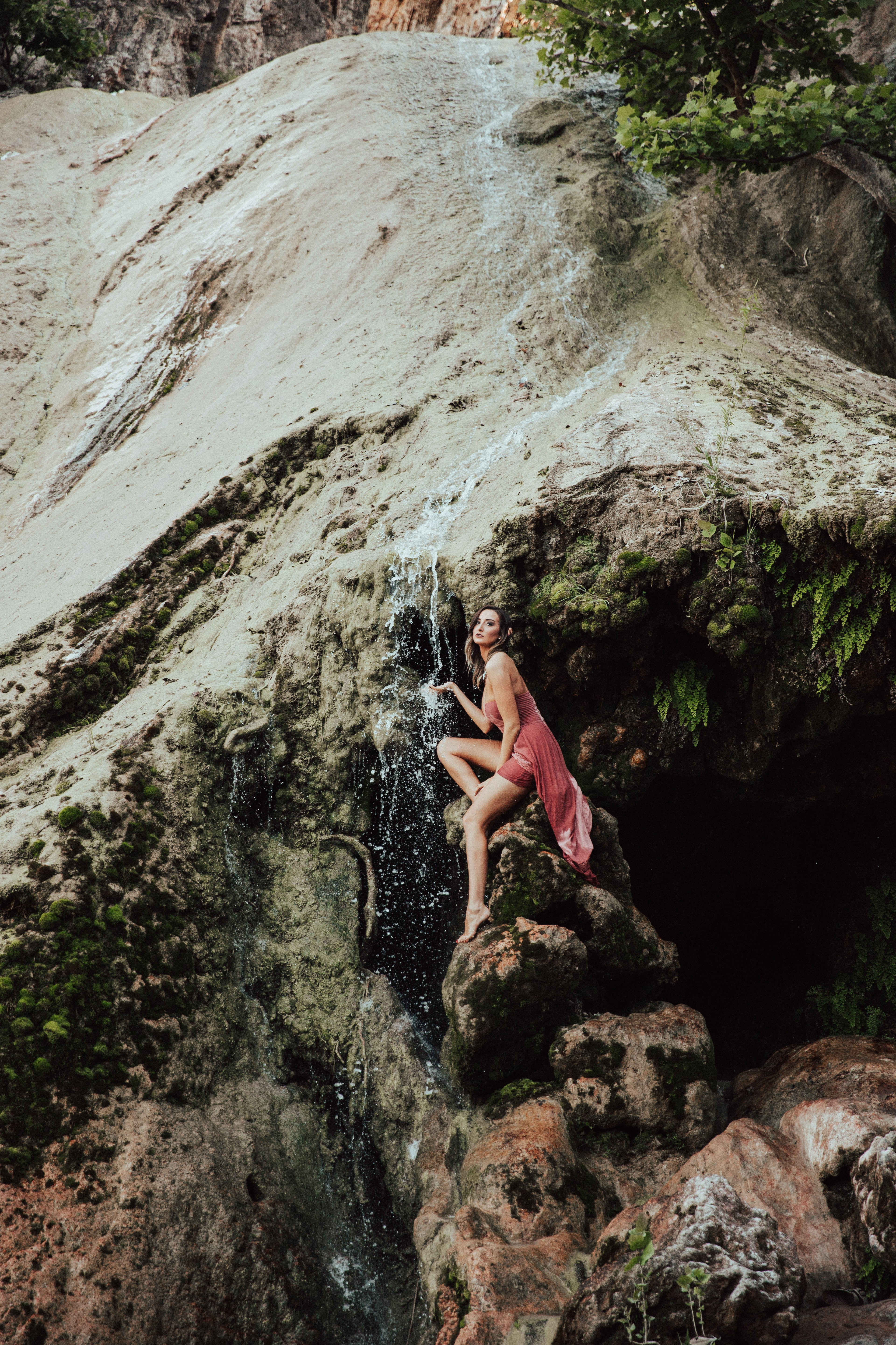 Woman posed like a water nymph near waterfall in a natural landscape