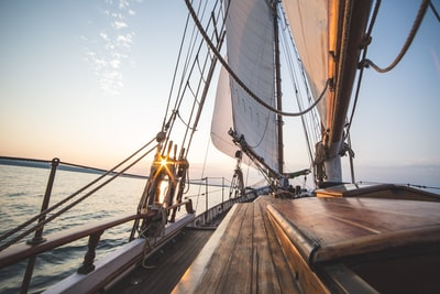 brown ship sailing on sea during daytime boat teams background