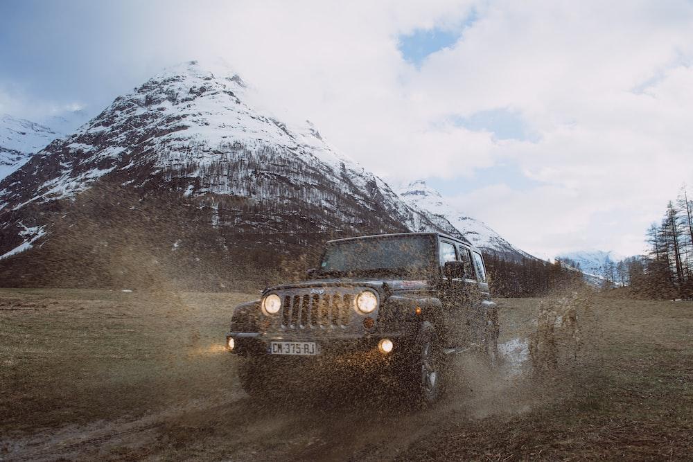 photo of gray Jeep Cherokee near snow-covered mountain
