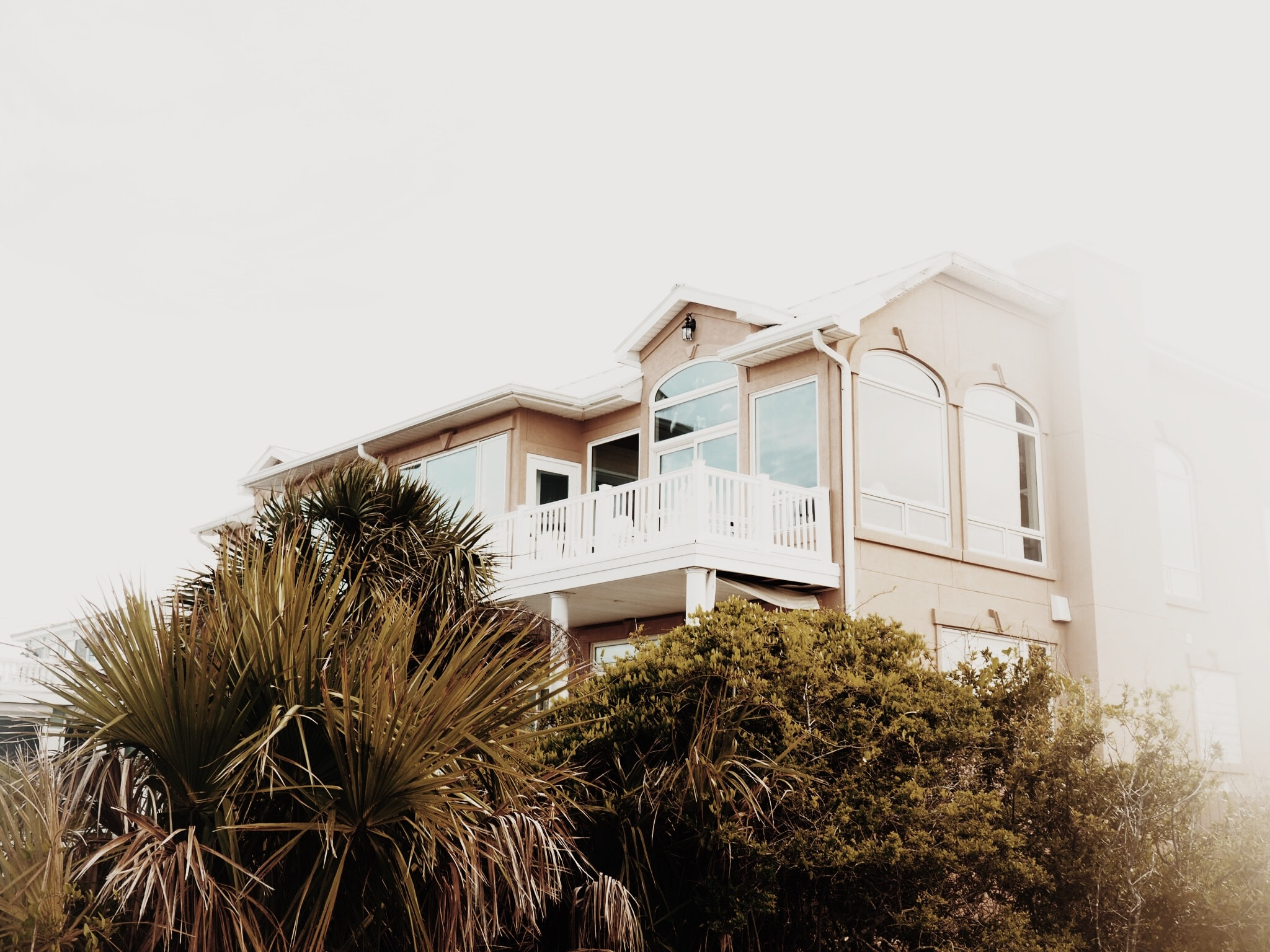 A beach house on Tybee Island surrounded by palm trees on a foggy day