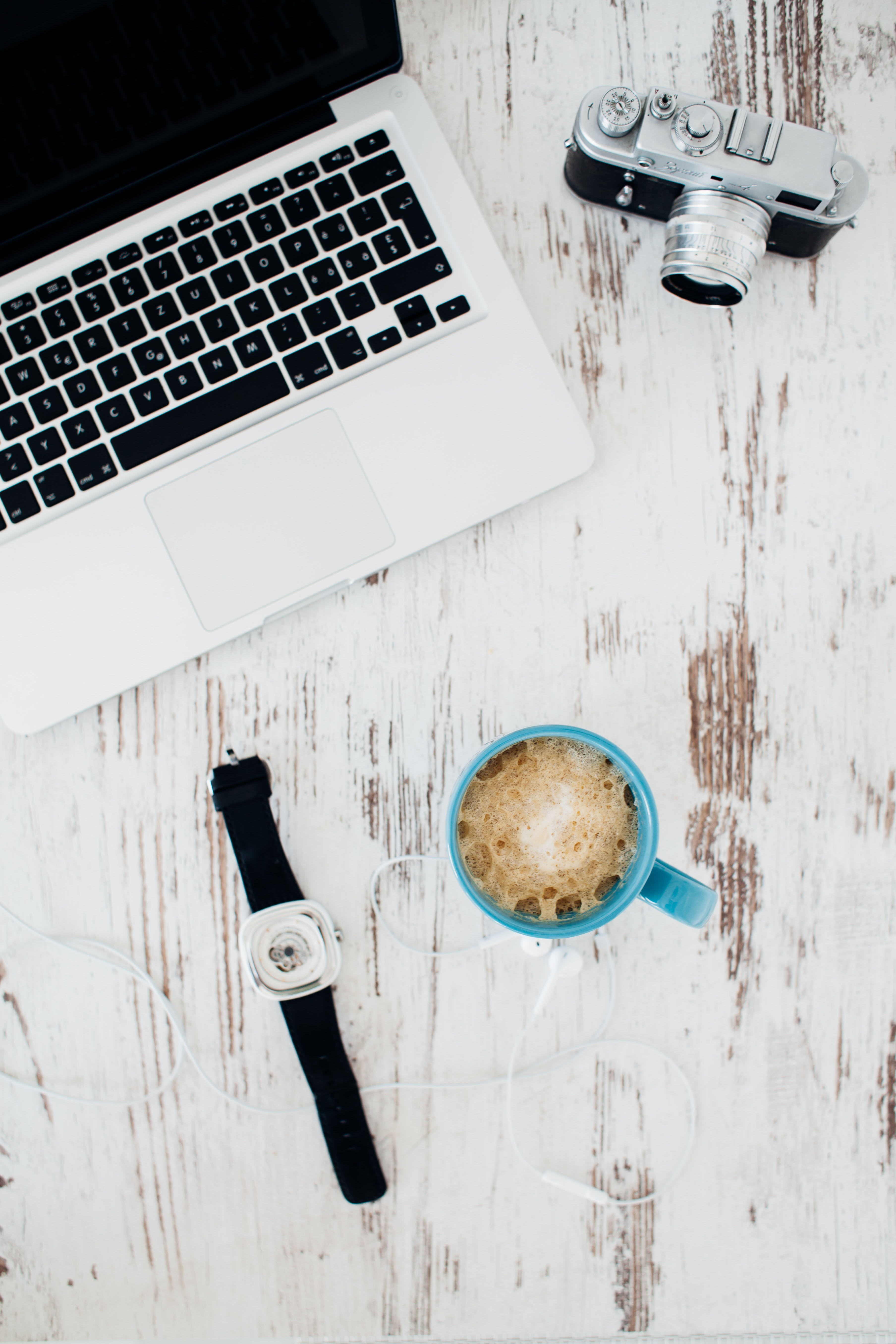 An overhead shot of a watch, a cup of coffee, a laptop and a camera on a wooden surface