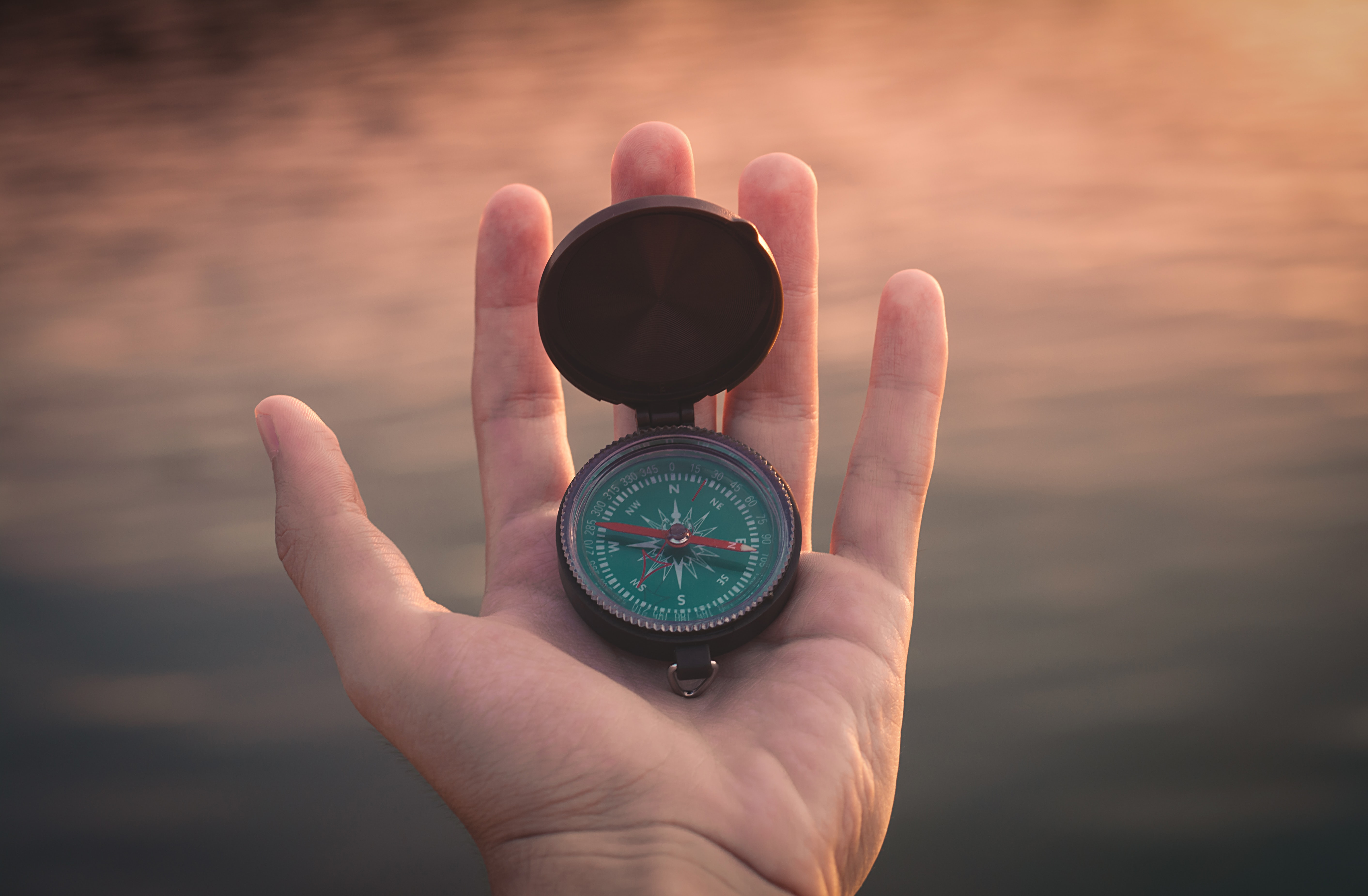 A compass is held in a man's left hand.