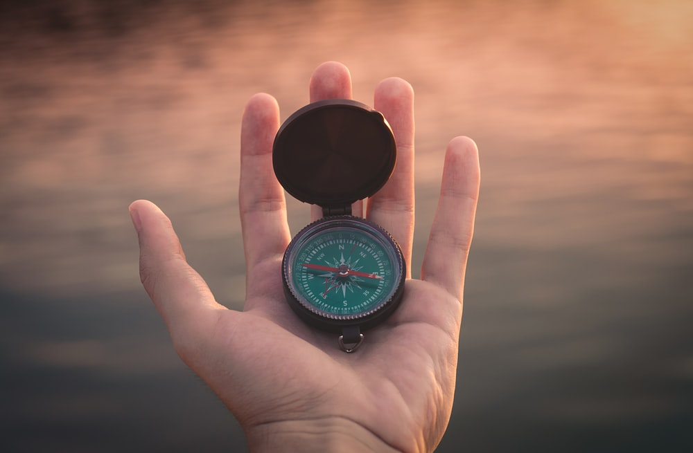 person holding black and green compass pointing to west