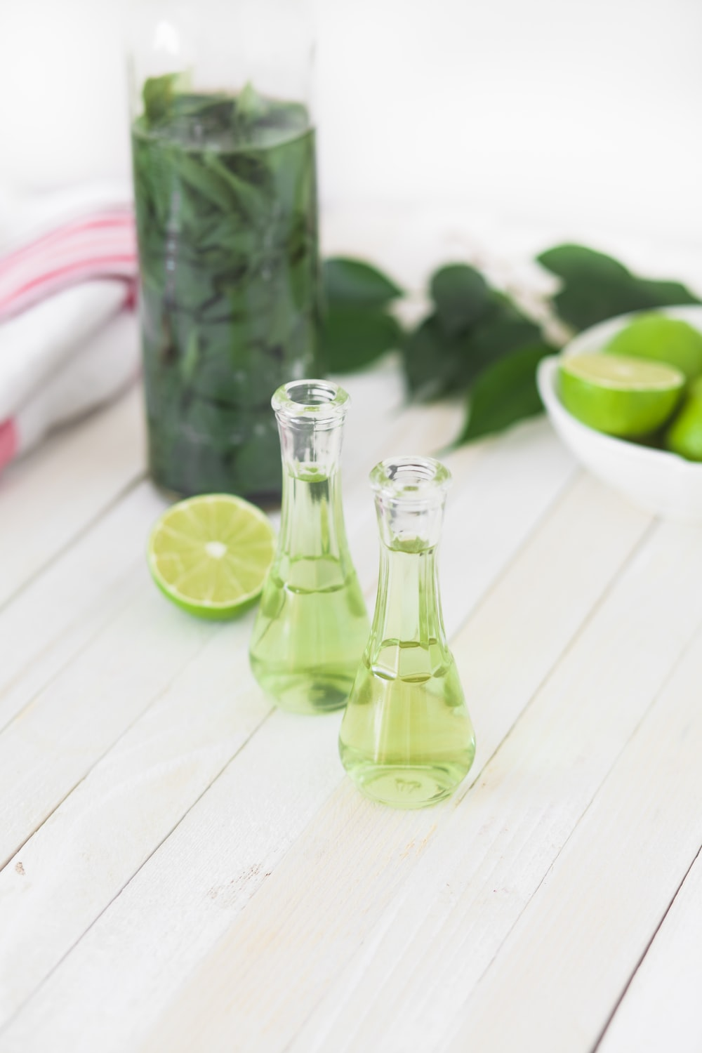 two clear glass bottles with lime juice on white wooden table