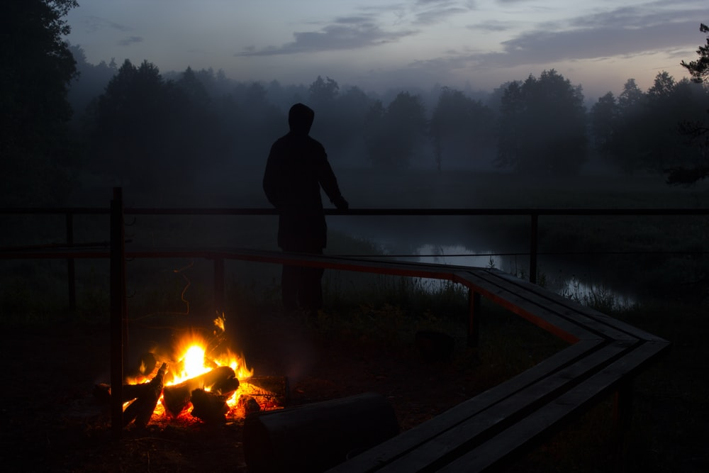 silhouette photo of a person standing near body of water and bonfire