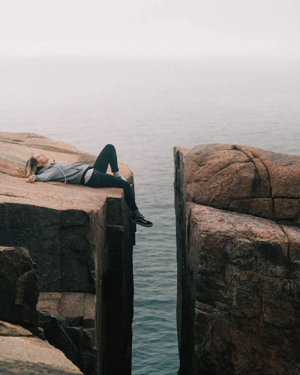 woman lying on top of cliff