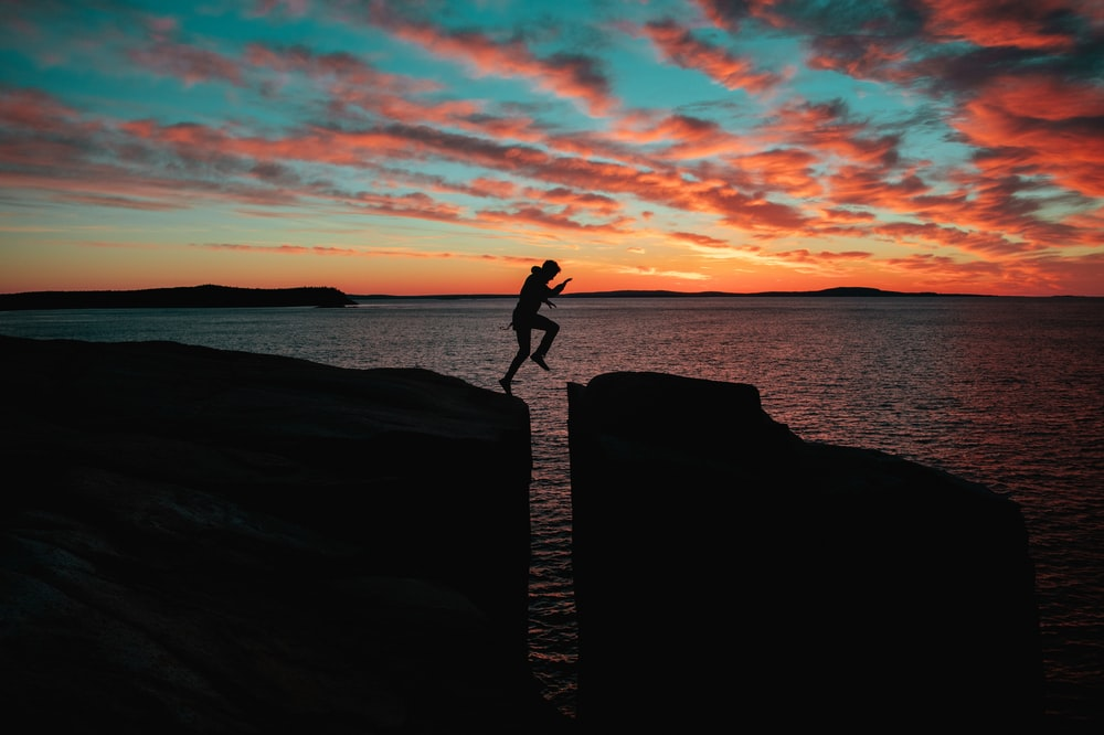 silhouette photo of a man jumps on to cliff near sea during sunset