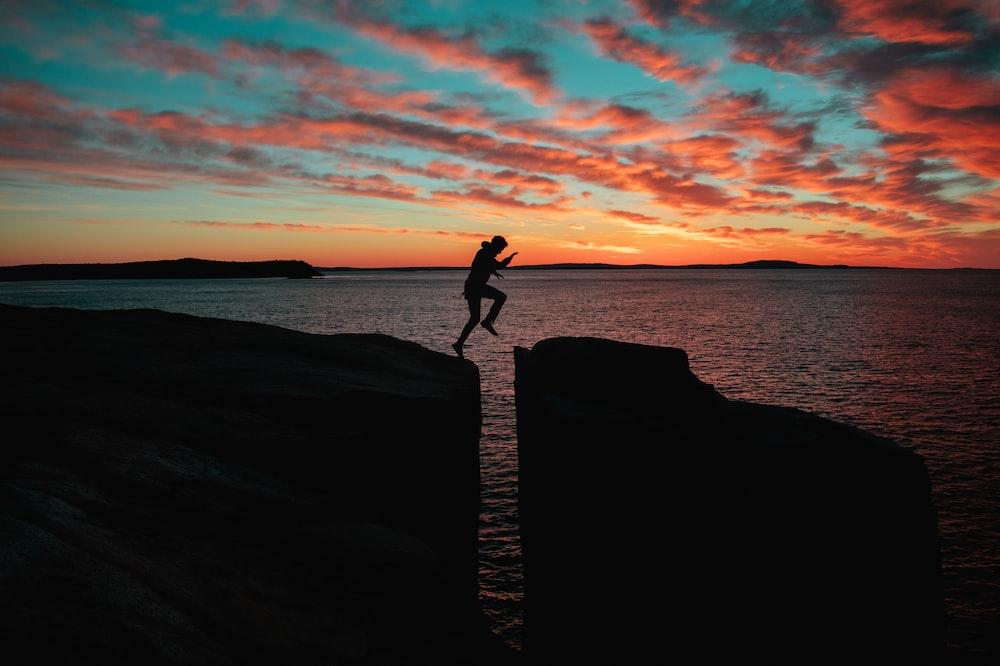 男のシルエット写真は日没時に海の近くの崖にジャンプします