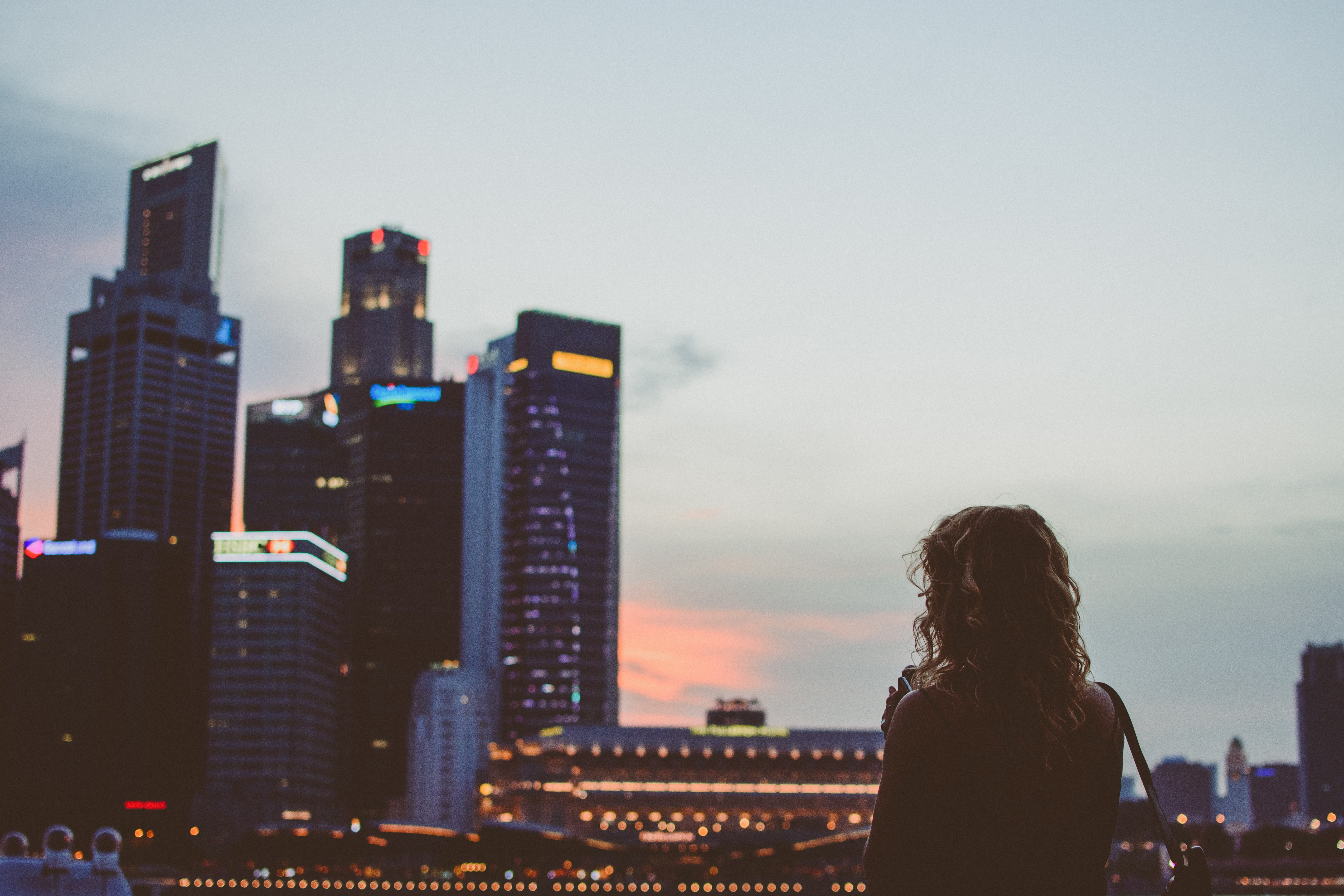 A woman looking at the skyline of Singapore during sunset