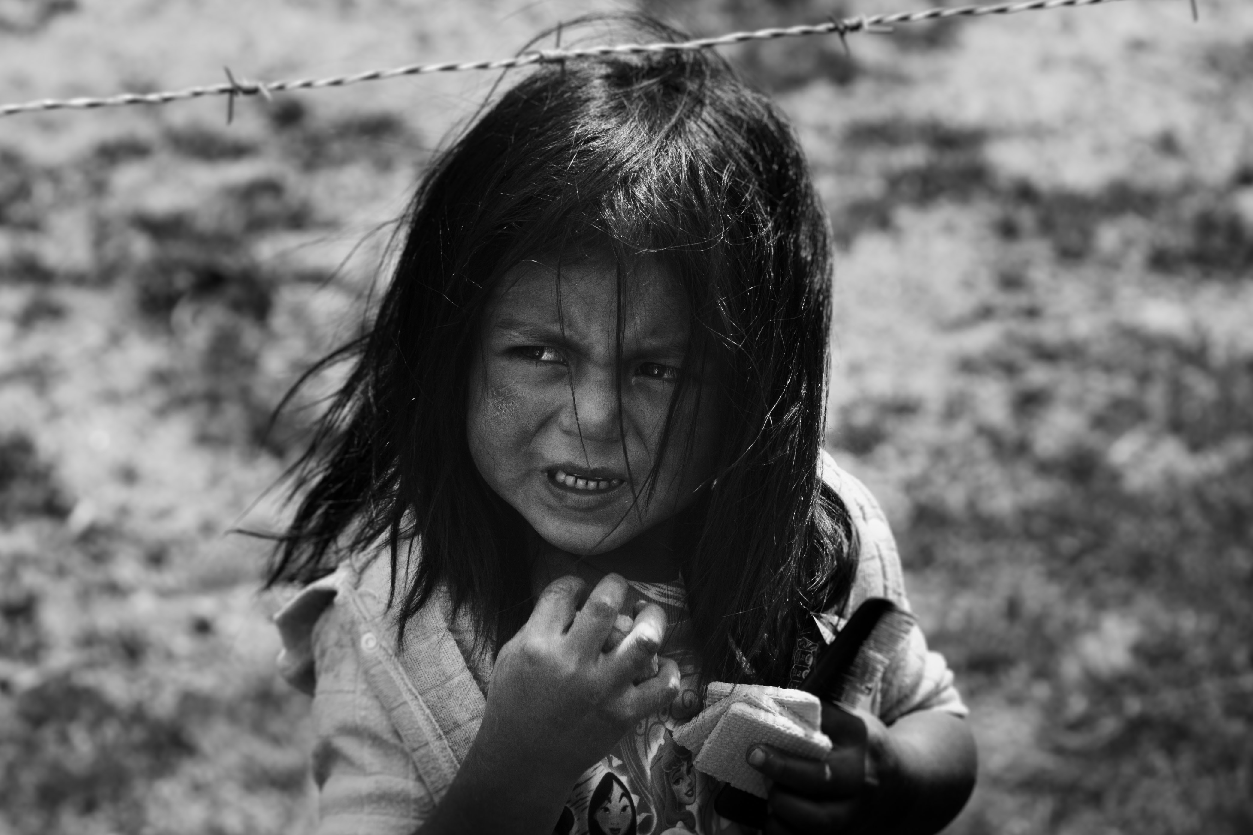 girl holding hair comb behind barbed wire