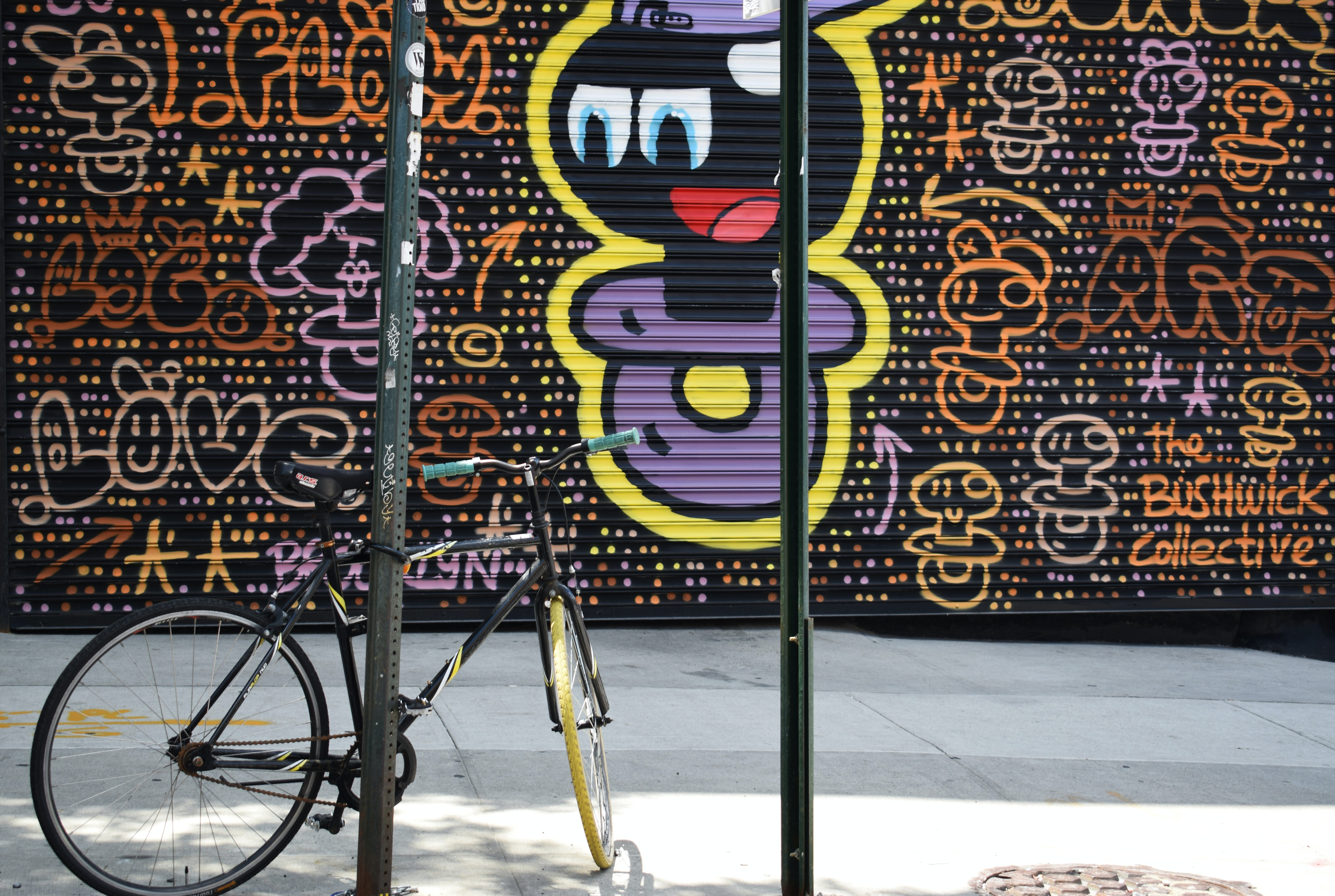Cartoonish colorful purple graffiti covering urban wall with bike leaning against post on sidewalk