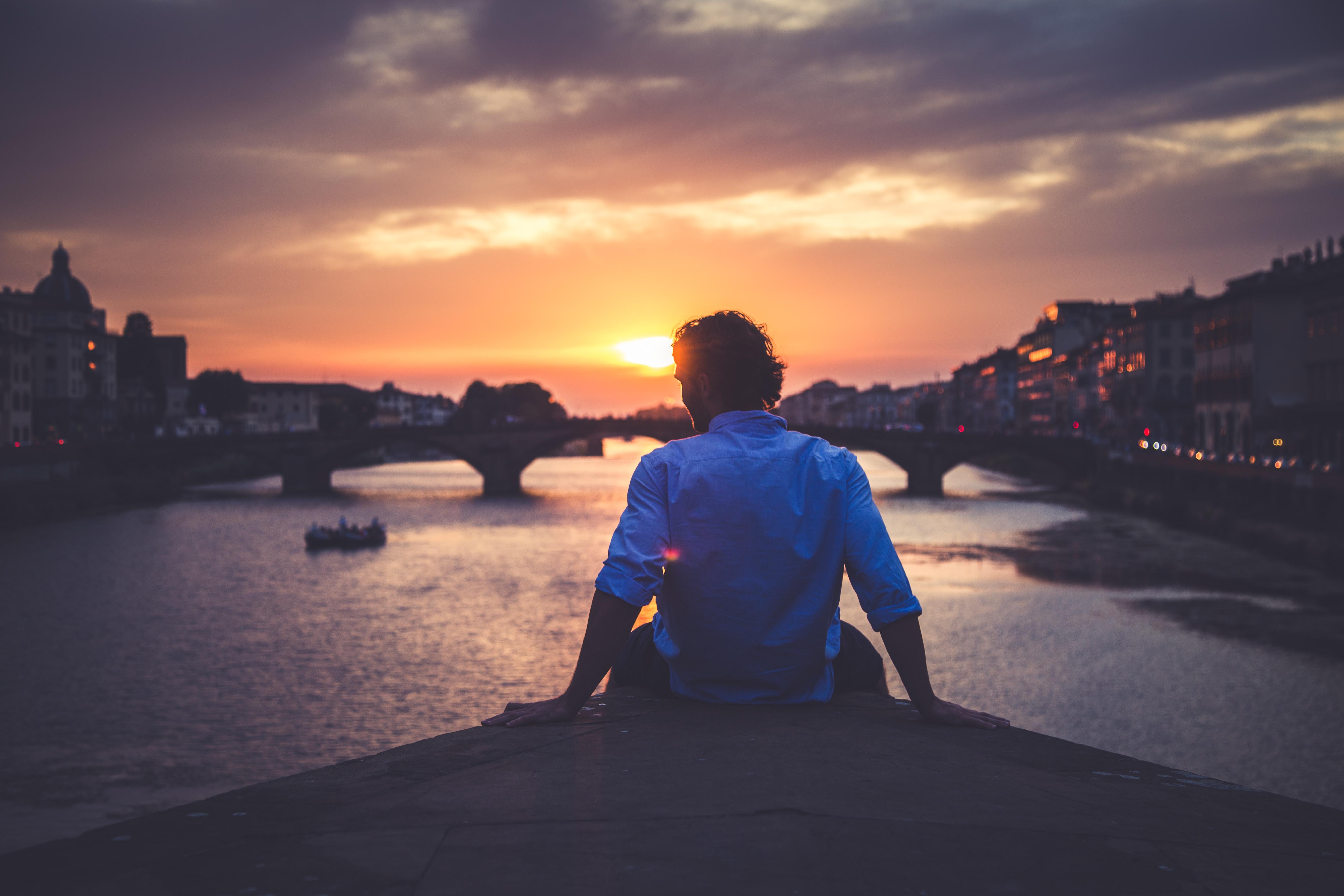 man wearing dress shirt sitting on dock near body of water during golden hour
