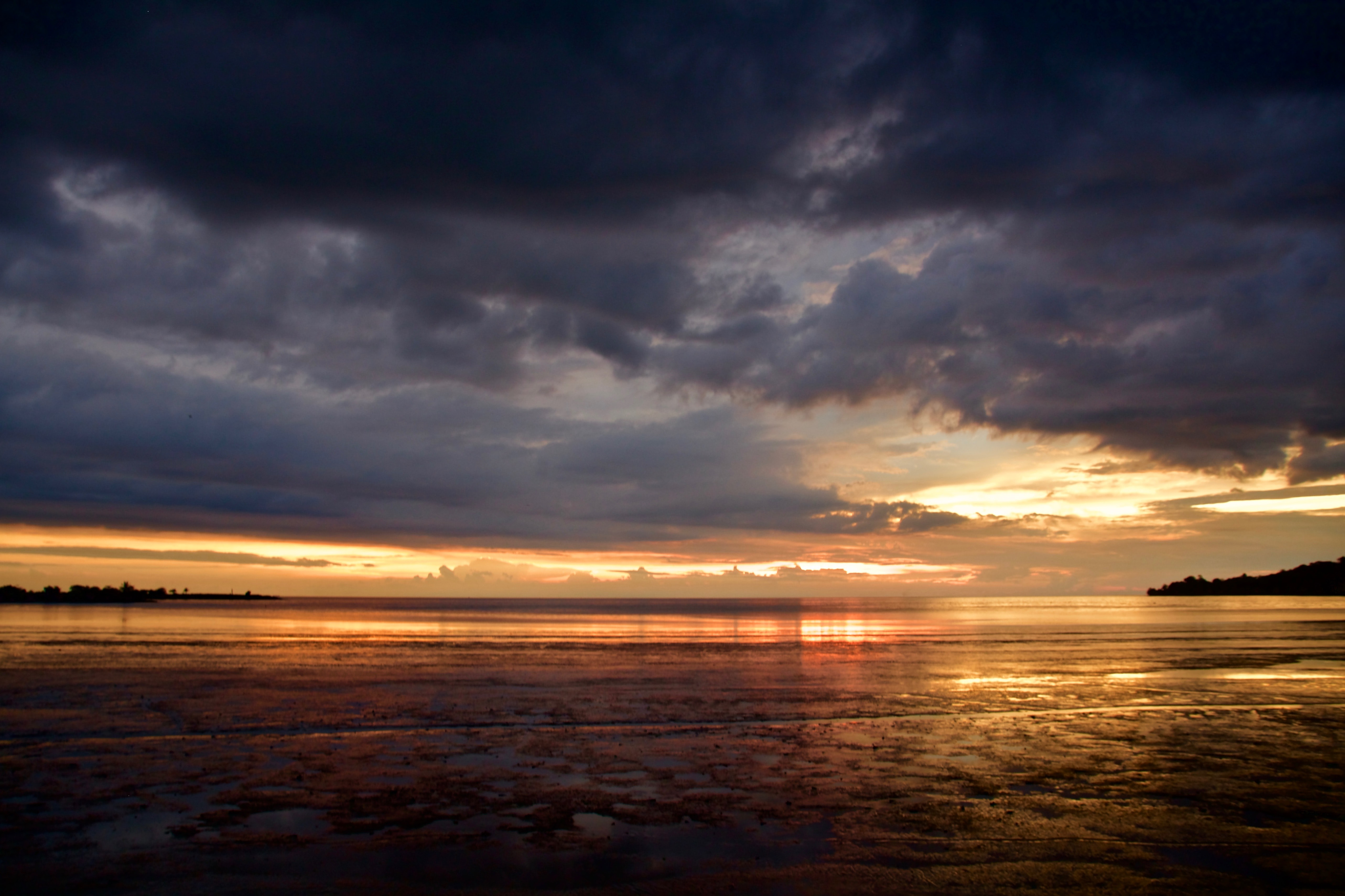 calm beach with brown sand under gray clouds during sunset