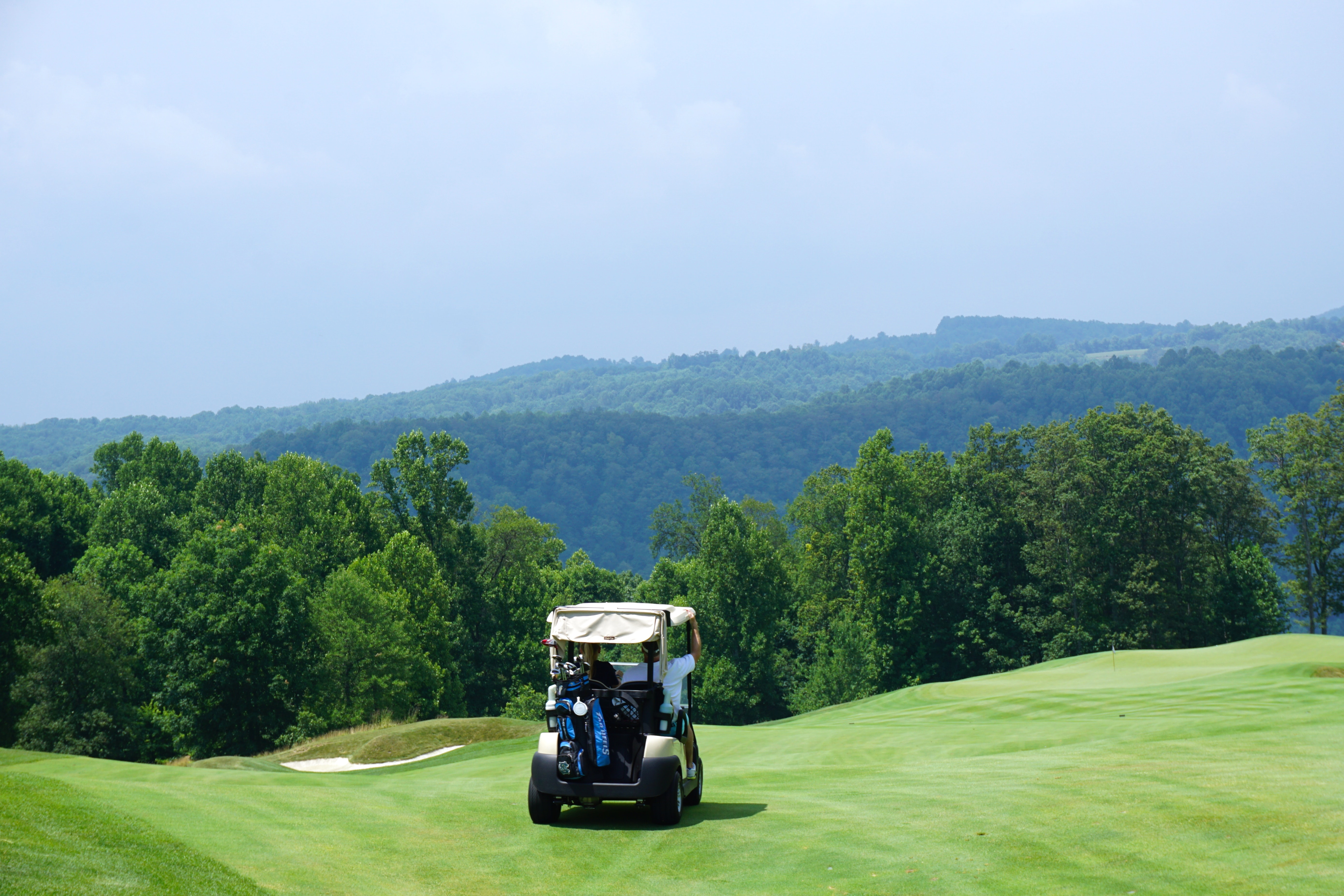 Golf cart drives on Highland Course grass in front of green trees and hills