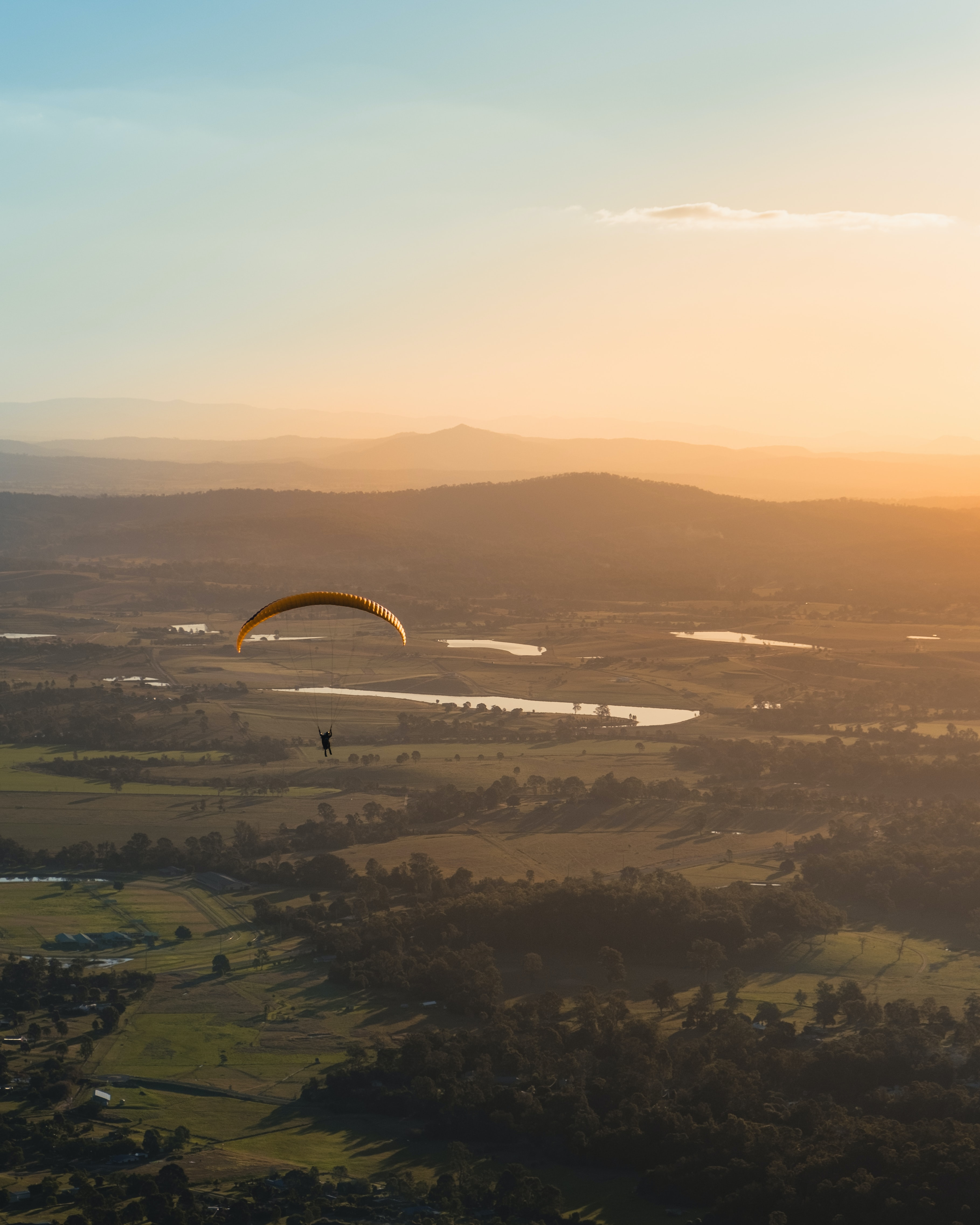 The aerial view of the gold coast and a person coming down in a parachute to it