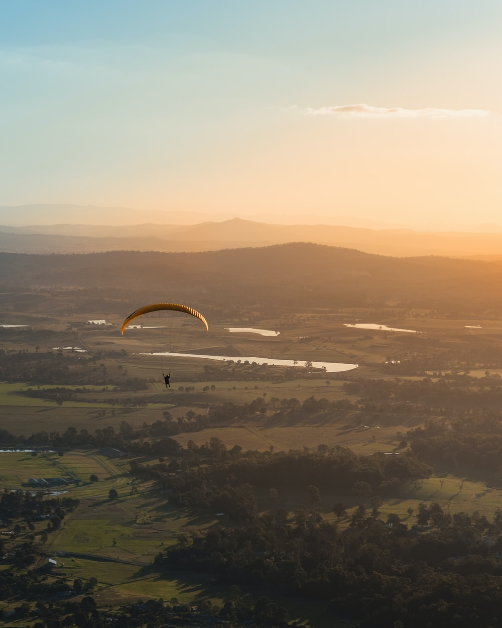 person paragliding above countryside during daytime