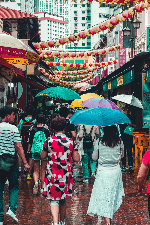 group of people walking at street with bazaar