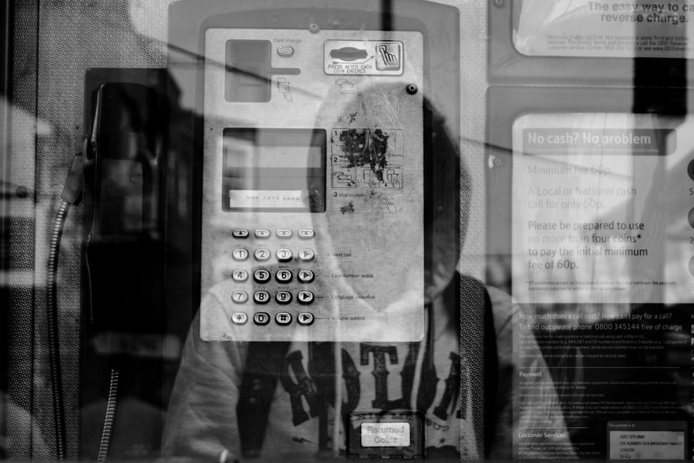grayscale photo of reflection of person wearing hoodie carrying backpack on glass telephone booth wall