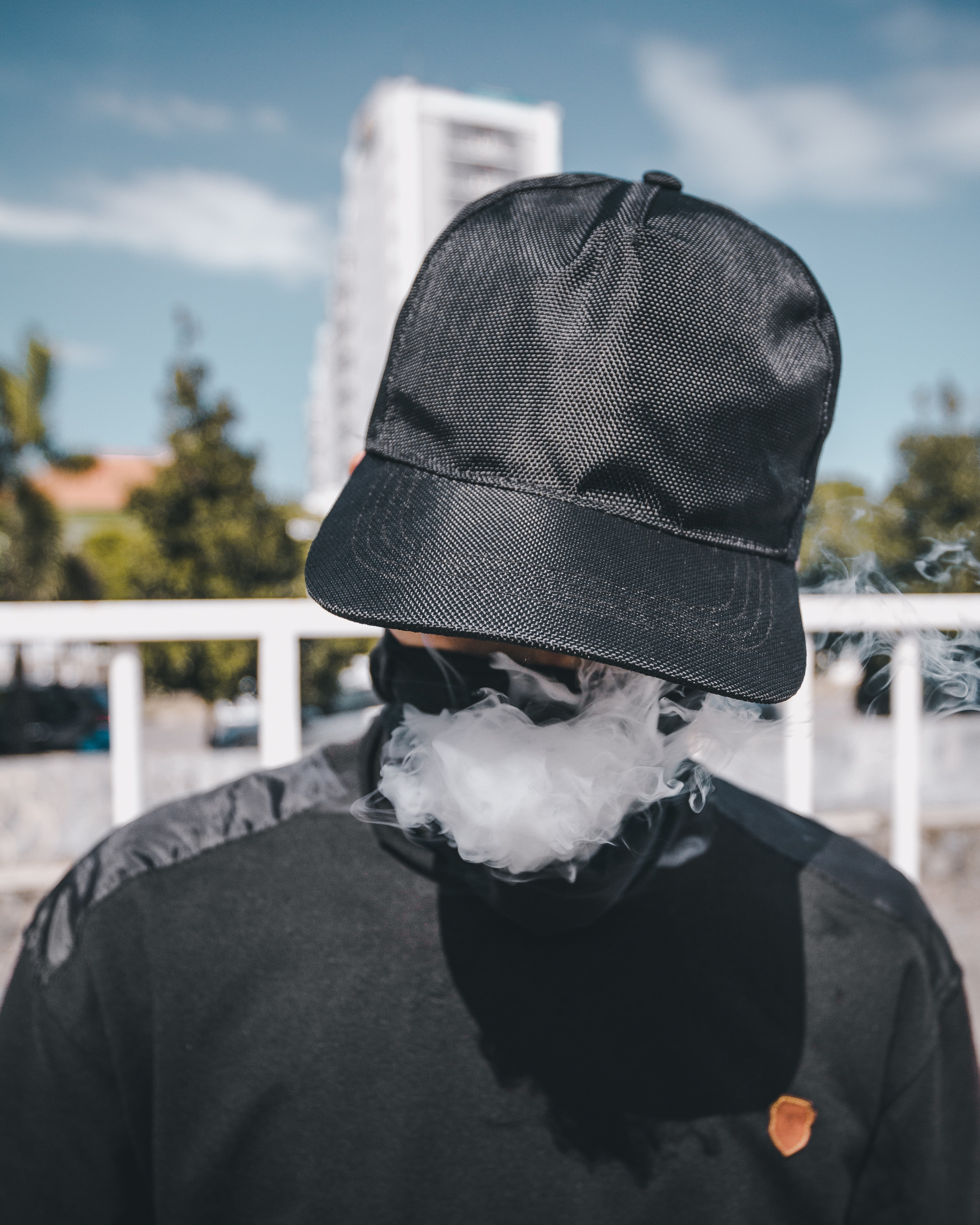 A person in a black baseball cap and covered face exhales smoke in Central Jakarta