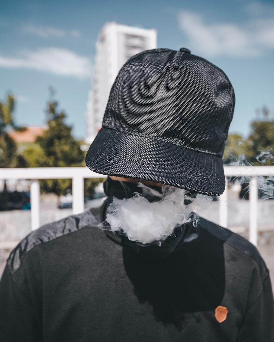 Hidden person exhaling smoke