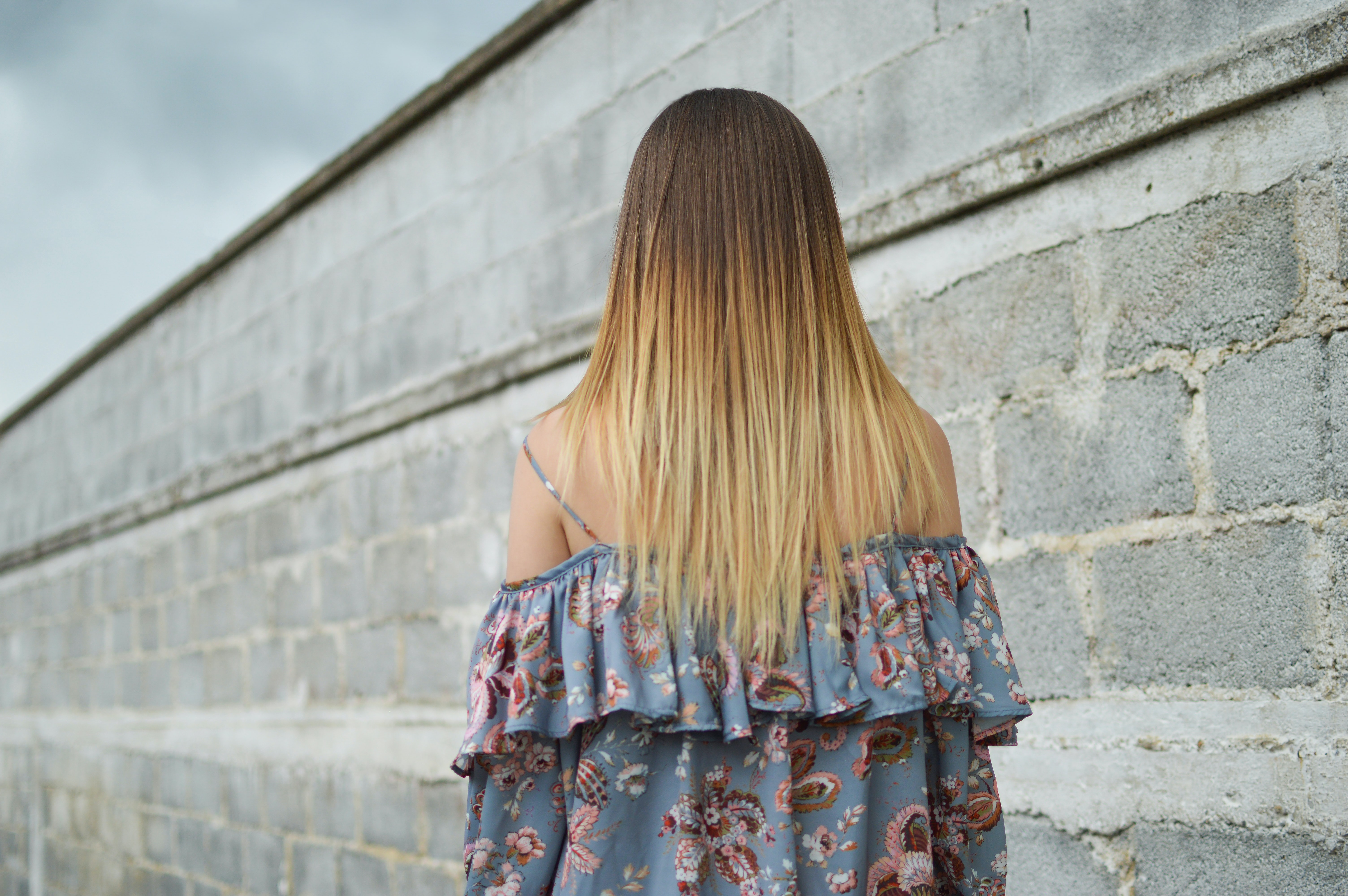 Brunette woman with blonde highlights a blue floral dress beside a stone wall under a gray sky