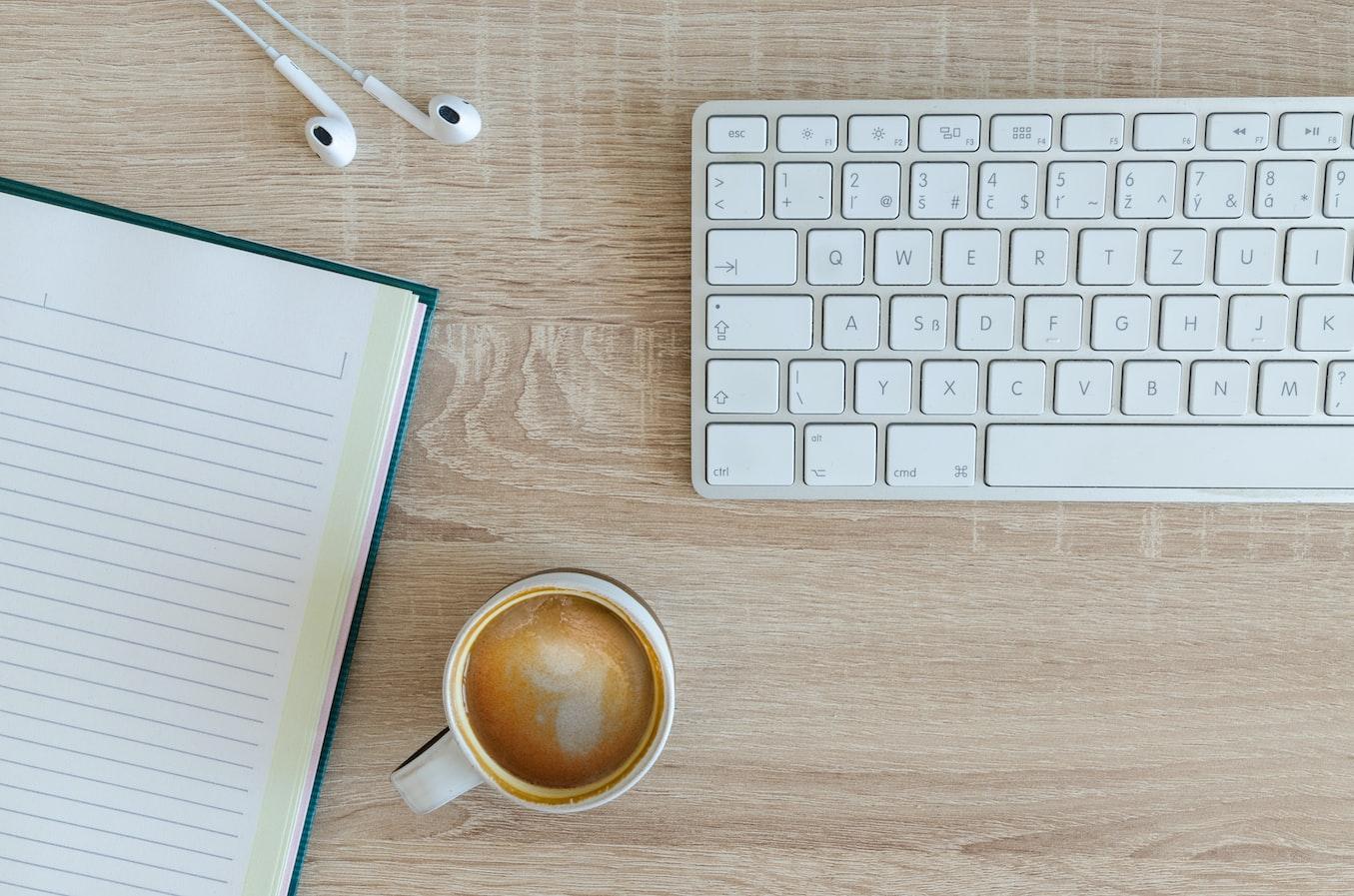 Stock image of a keyboard, earphones, notebook and a coffee mug.