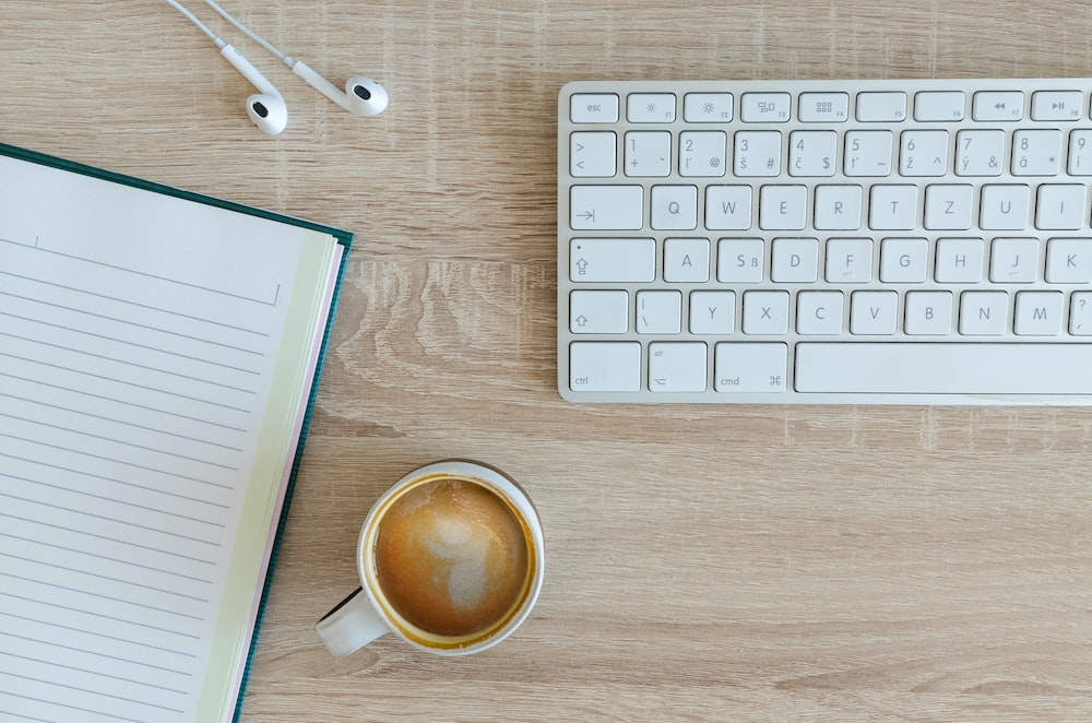 An overhead shot of a cup of coffee, a notebook and a keyboard on a wooden desk