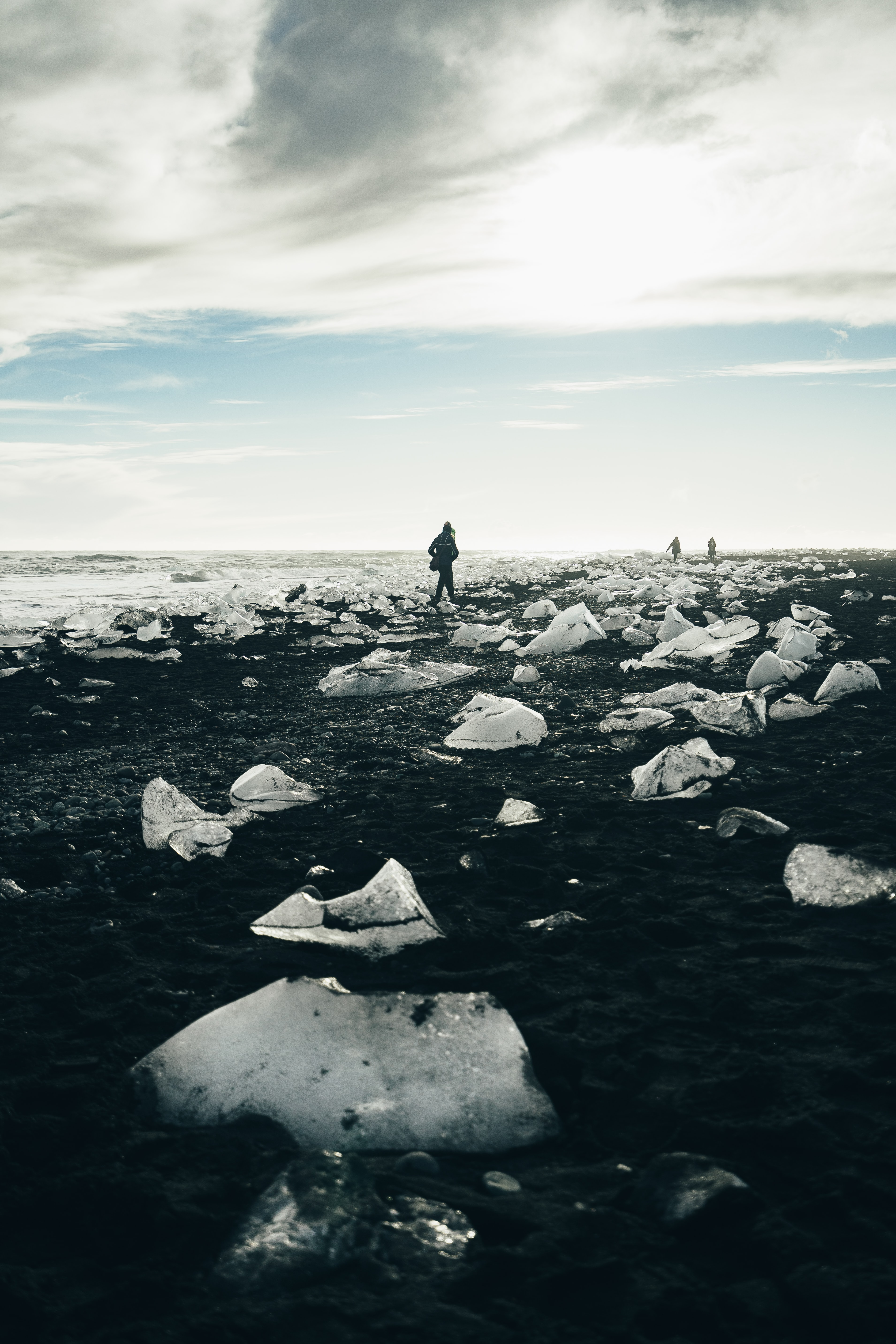 Three people walk down a rocky beach covered in melting ice