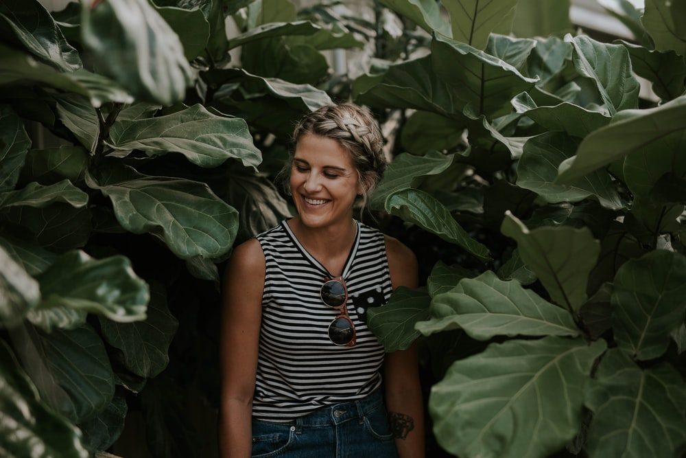 woman wearing black and white striped sleeveless shirt surrounded by green plants smiling posting for photo