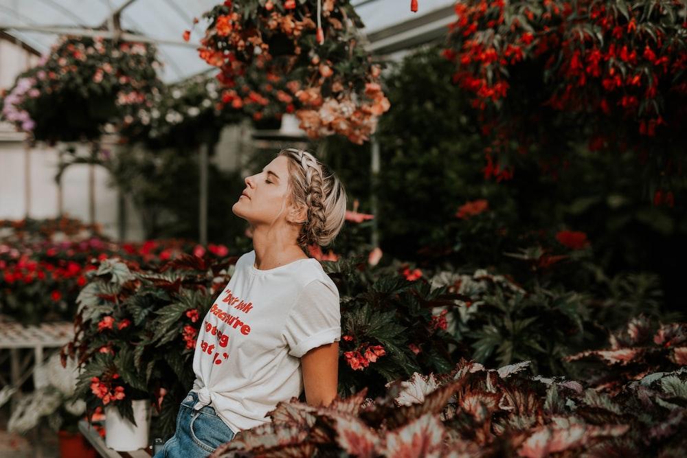 woman wearing white shirt standing near the flower