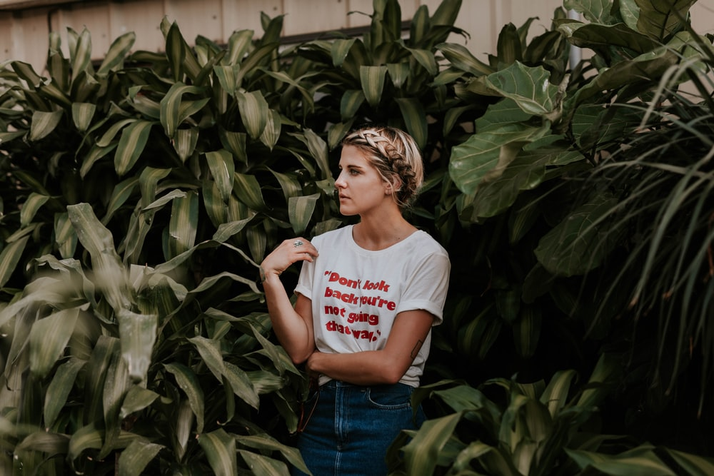 woman in white shirt standing and surrounded by green plants