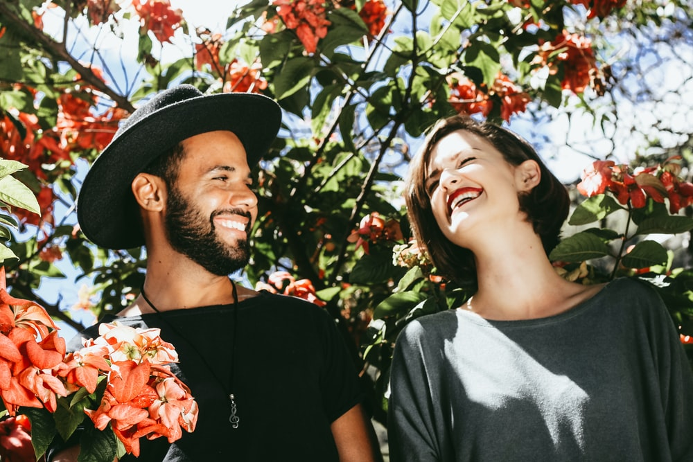 man and woman surrounded by red and green floral trees during daytime
