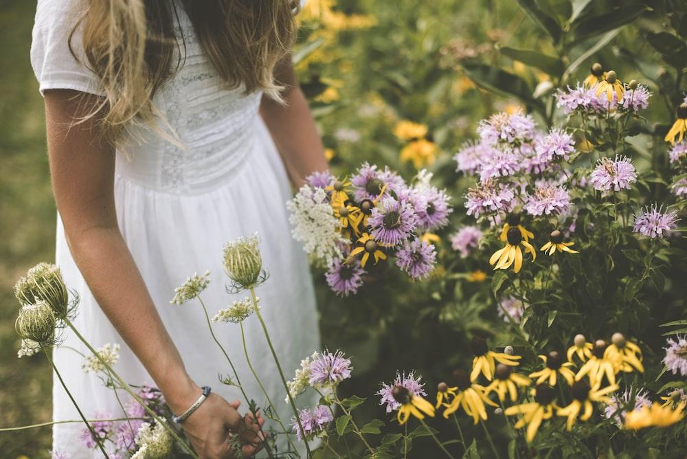 woman wearing white dress picking petaled flower