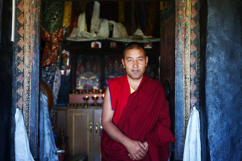 buddhist monk standing behind brown wooden cabinet