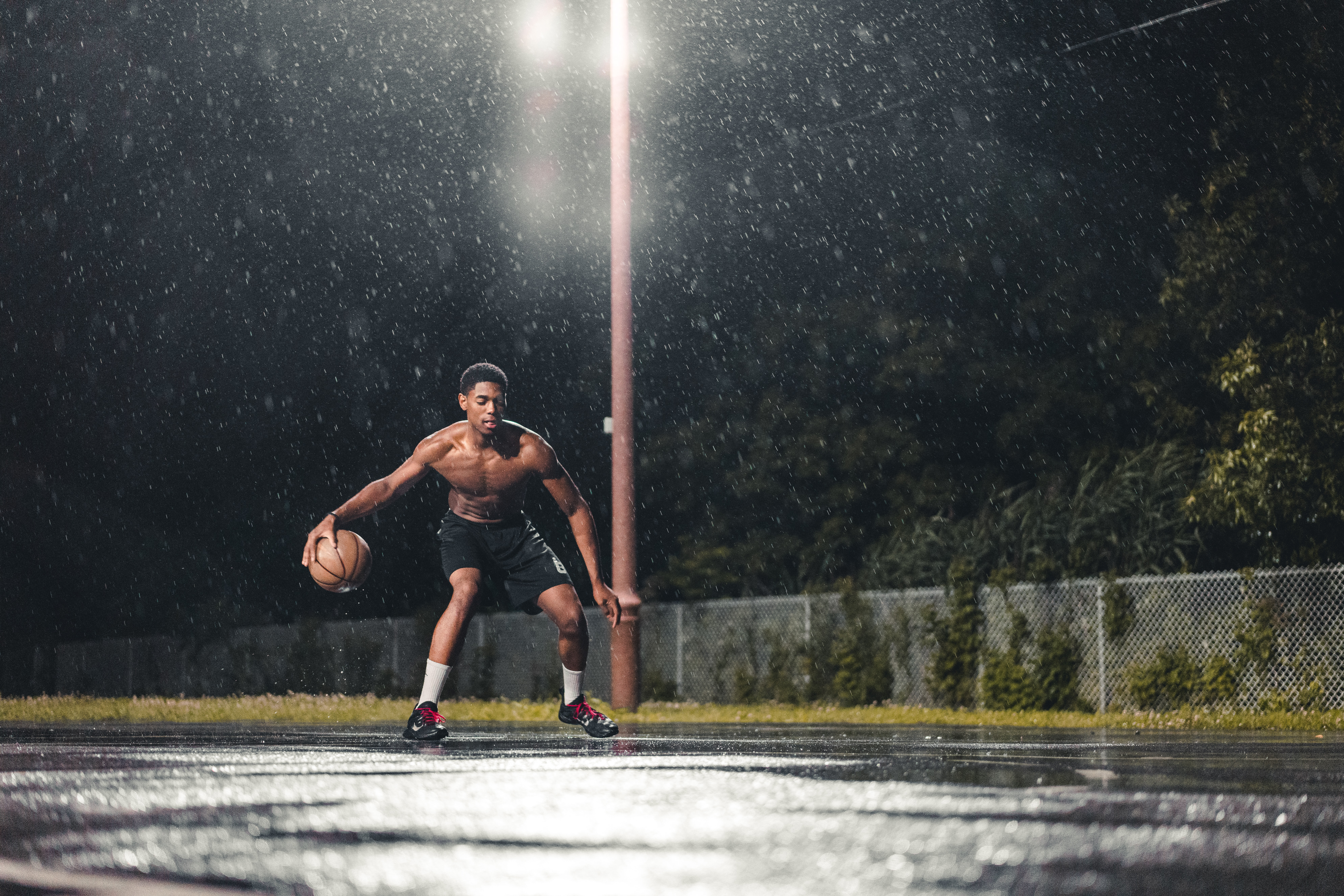 Athletic man playing basketball alone on a court in the rain