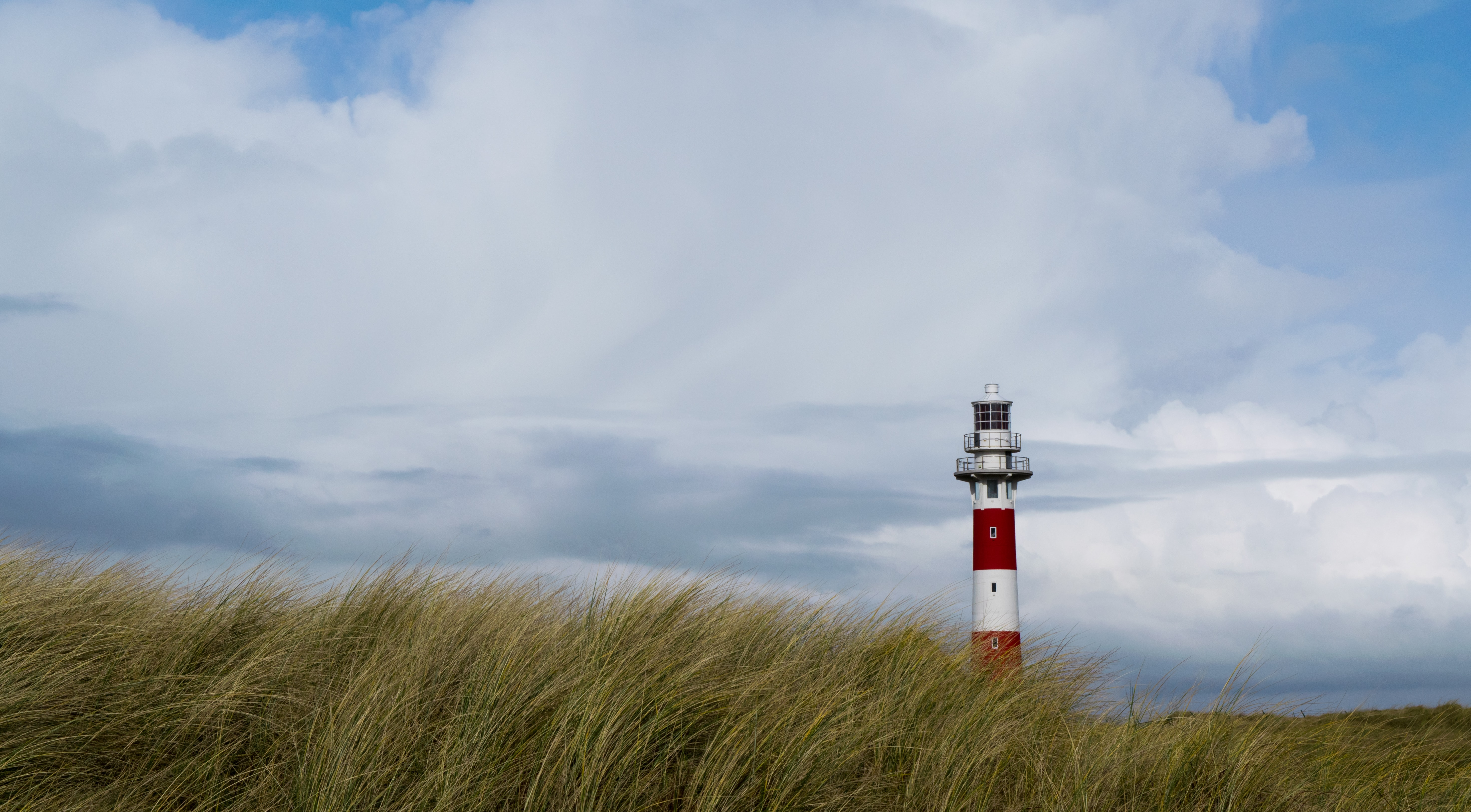 white and red lighthouse near grassland under white clouds at daytime