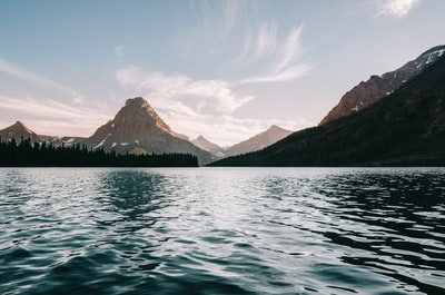 body of water near body trees and mountain glacier national park teams background