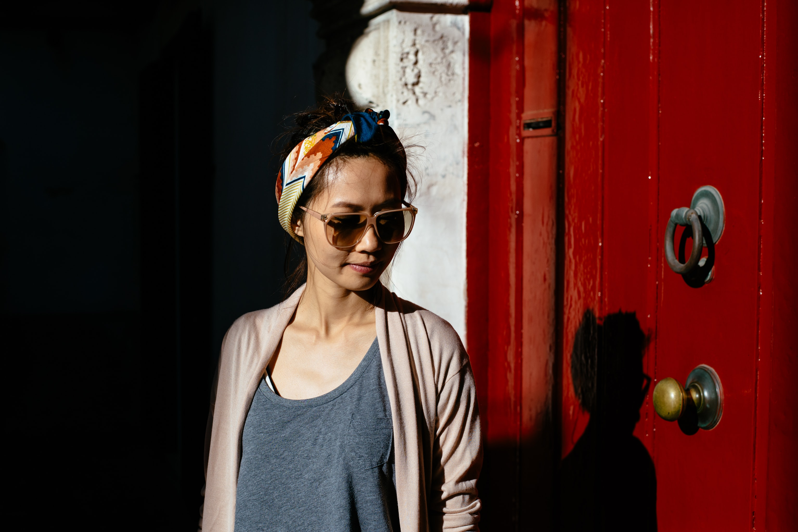 A woman wearing a hairband and sunglasses has her shadow cast on the red wooden door.