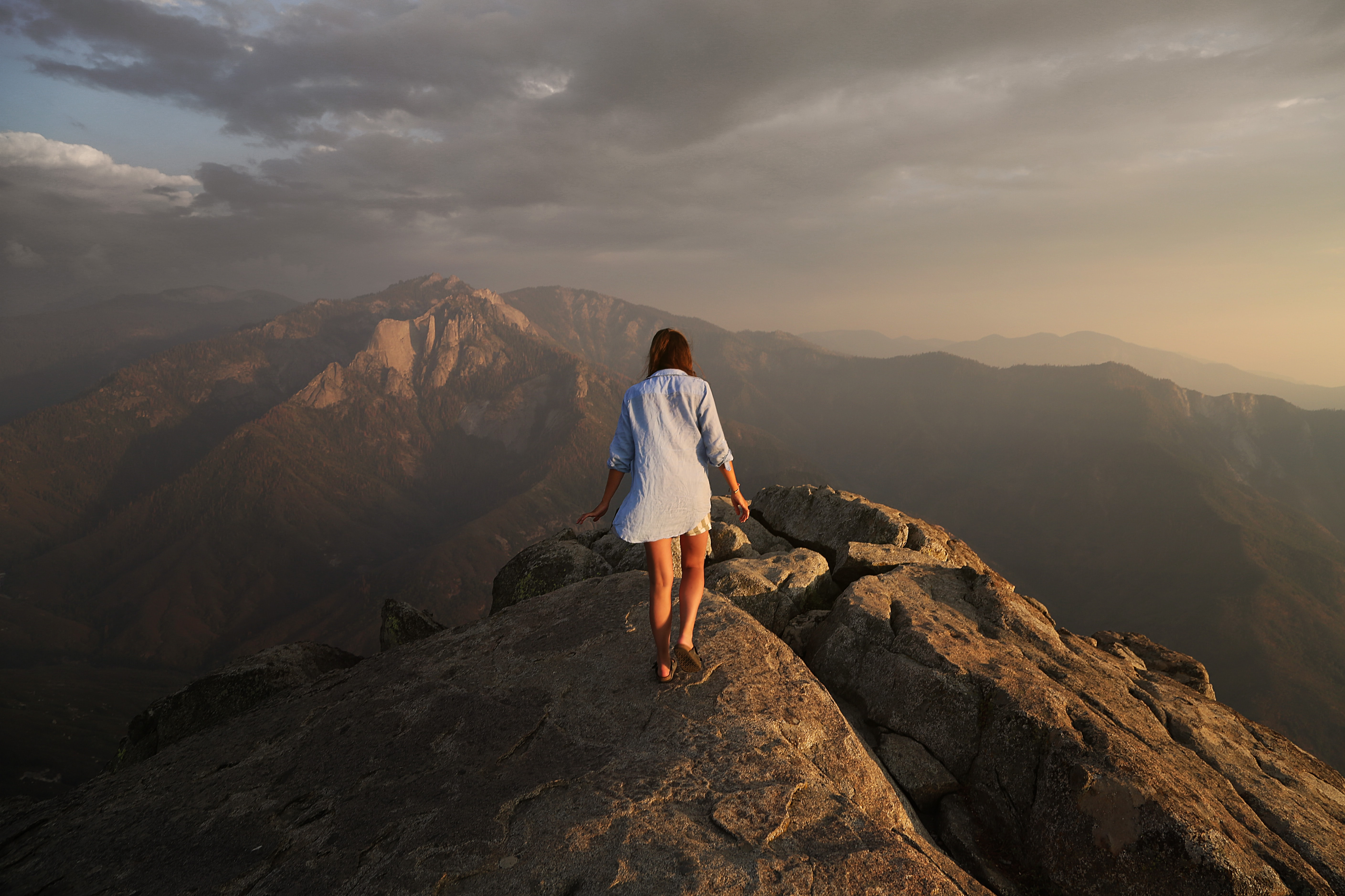 woman walking on grey rock mountain