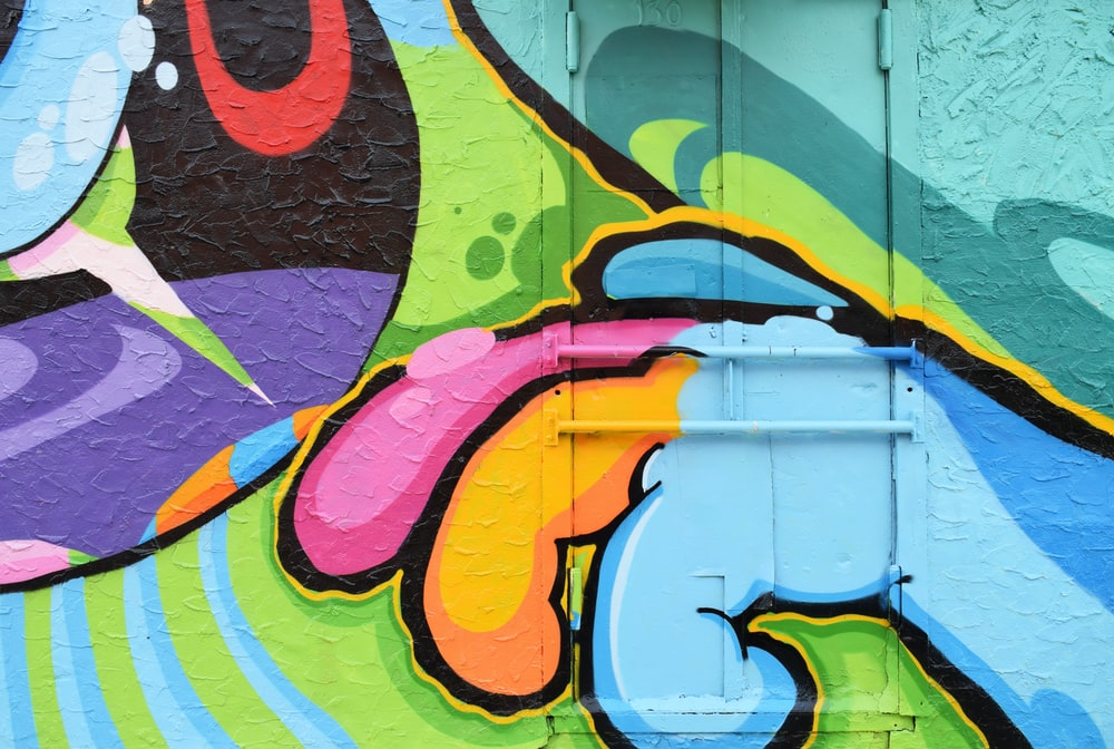 Brightly colored urban street art graffiti of cartoon monster mouth and hand