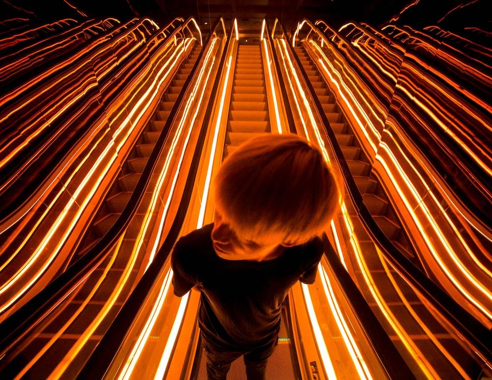 man on escalator with light