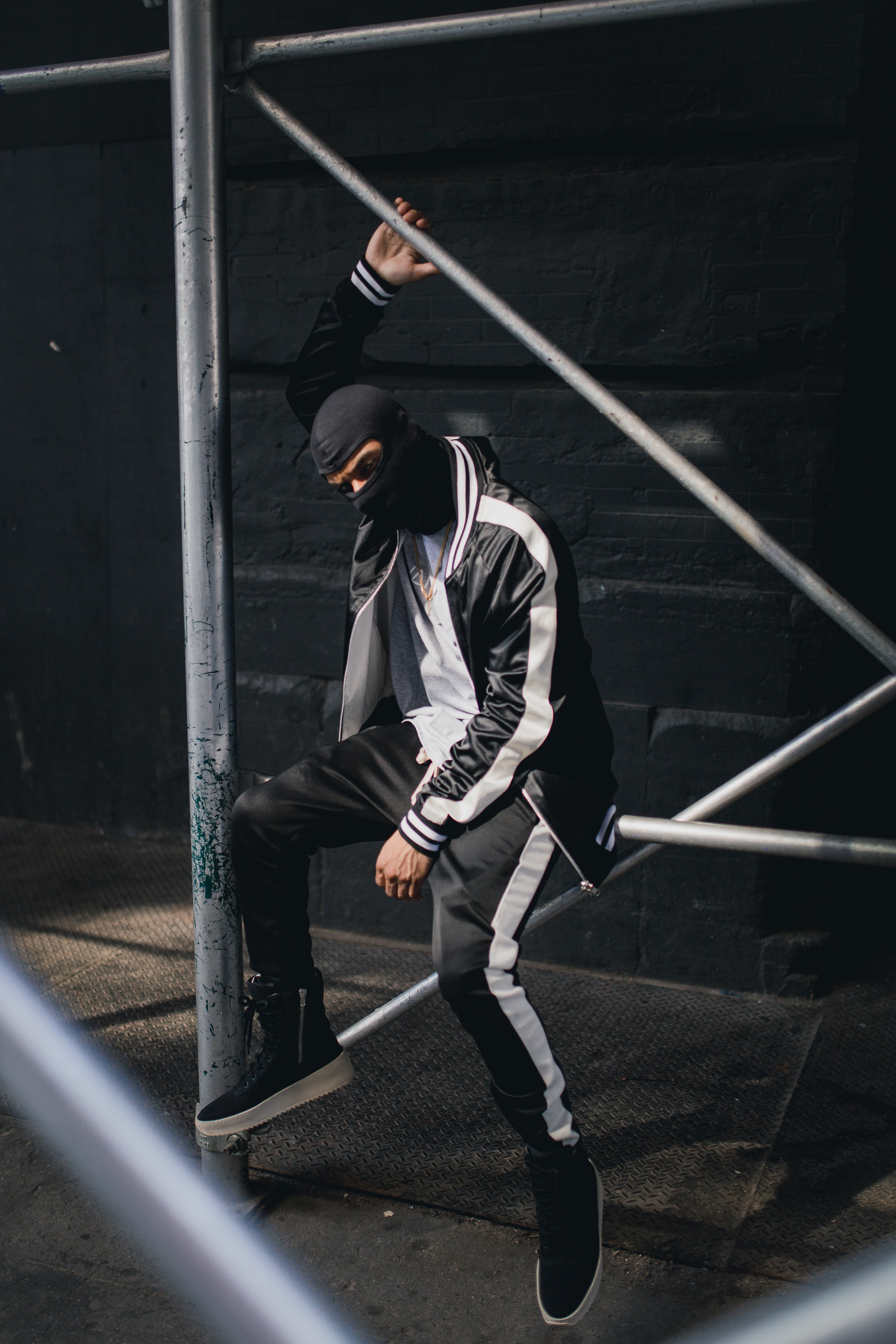 A person in a tracksuit and black facemask sits on a metal railing